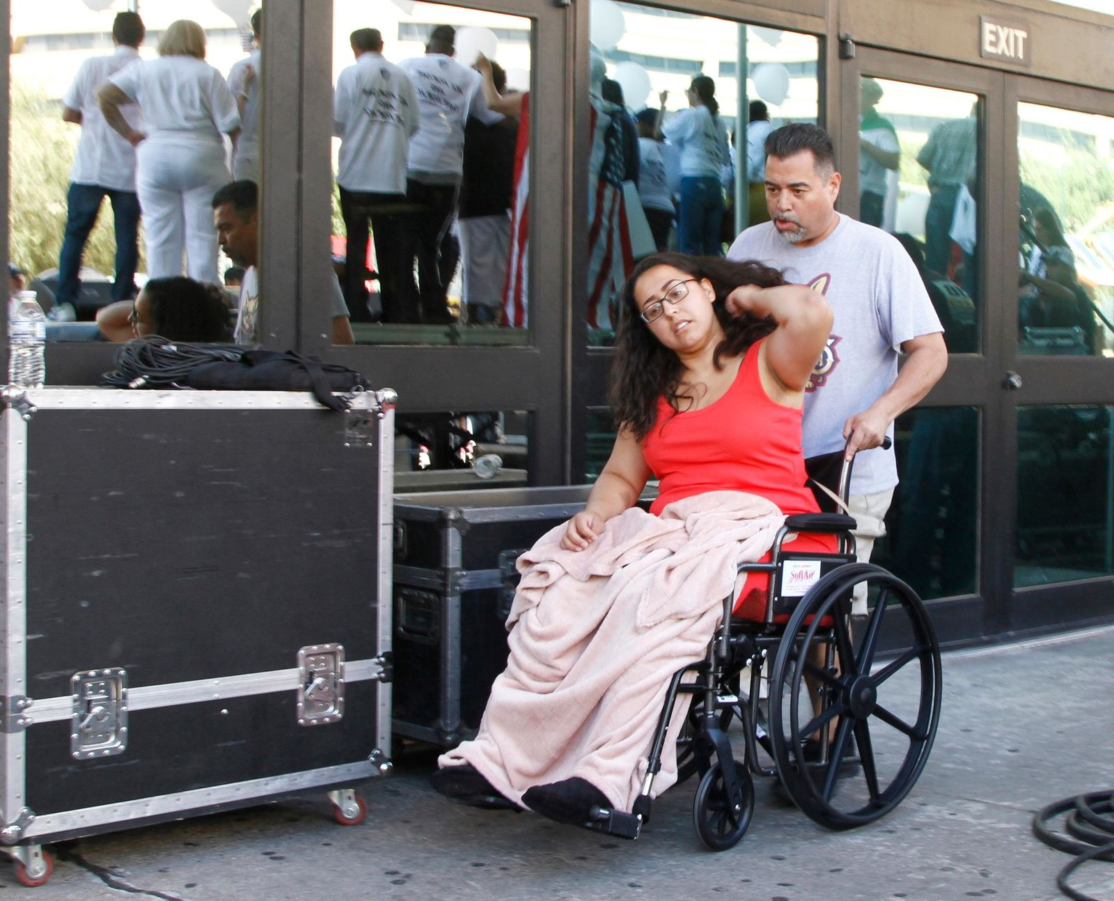 "Jessica Coca Garcia is wheeled away after speaking at League of United Latin American Citizens' ""March For a United America,"" in El Paso, Texas, on Saturday, Aug. 8, 2019, a week after she and her husband were injured by bullets during a mass shooting. More than 100 people marched through the Texas border denouncing racism and calling for stronger gun laws one week after several people were killed in a mass shooting that authorities say was carried out by a man targeting Mexicans.  (AP Photo/Cedar Attanasio)"