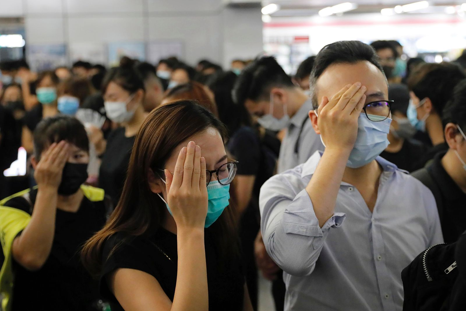 "Demonstrators cover their eyes in remembrance of a woman who suffered a serious eye injury in a previous demonstration, during a protest at the Yuen Long MTR station in Hong Kong, Wednesday, Aug. 21, 2019.  Japan's top diplomat on Tuesday told his Chinese counterpart that Japan is ""deeply concerned"" about the continuing protests in Hong Kong. (AP Photo/Kin Cheung)"