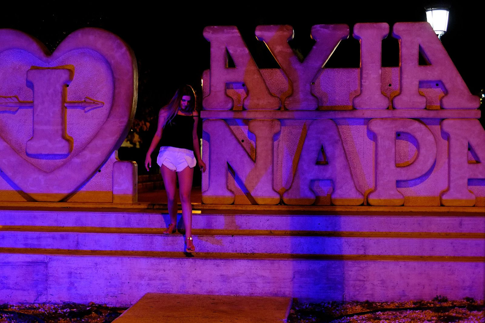 "A tourist walks at a sculpture that read ""I Love Ayia Napa"" after posing for photos in the southeast resort of Ayia Napa in the eastern Mediterranean island of Cyprus late Wednesday, July 17, 2019.{ } (AP Photo/Petros Karadjias)"