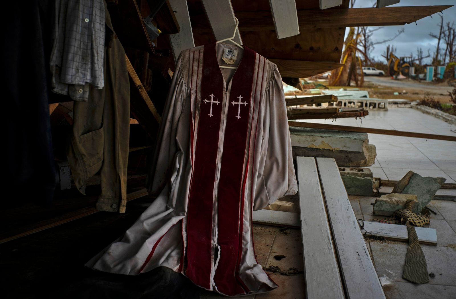 Priest's mass vestments hang in the rubble of a destroyed house by Hurricane Dorian in Pelican Point, Grand Bahama, Bahamas, Saturday Sept. 14, 2019. (AP Photo/Ramon Espinosa)