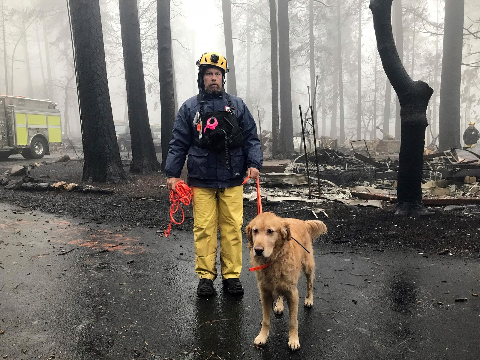 Eric Darling and his dog Wyatt are part of a search team from Orange County in Southern California who are among several teams conducting a second search of a mobile home park after the deadly Camp Fire in Paradise, Calif., Friday, Nov. 23, 2018. (AP Photo/Kathleen Ronayne)