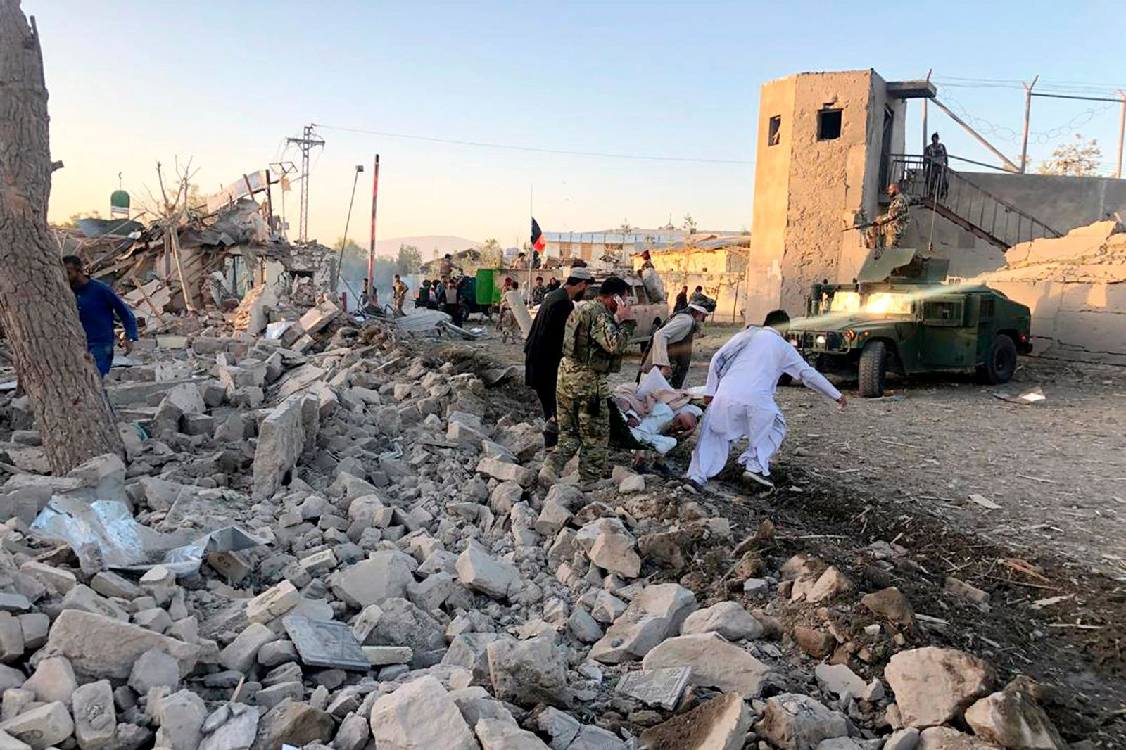 Afghan security members and people work at the site of a suicide attack in Zabul, Afghanistan, Thursday, Sept. 19, 2019.. (AP Photo/Ahmad Wali Sarhadi)