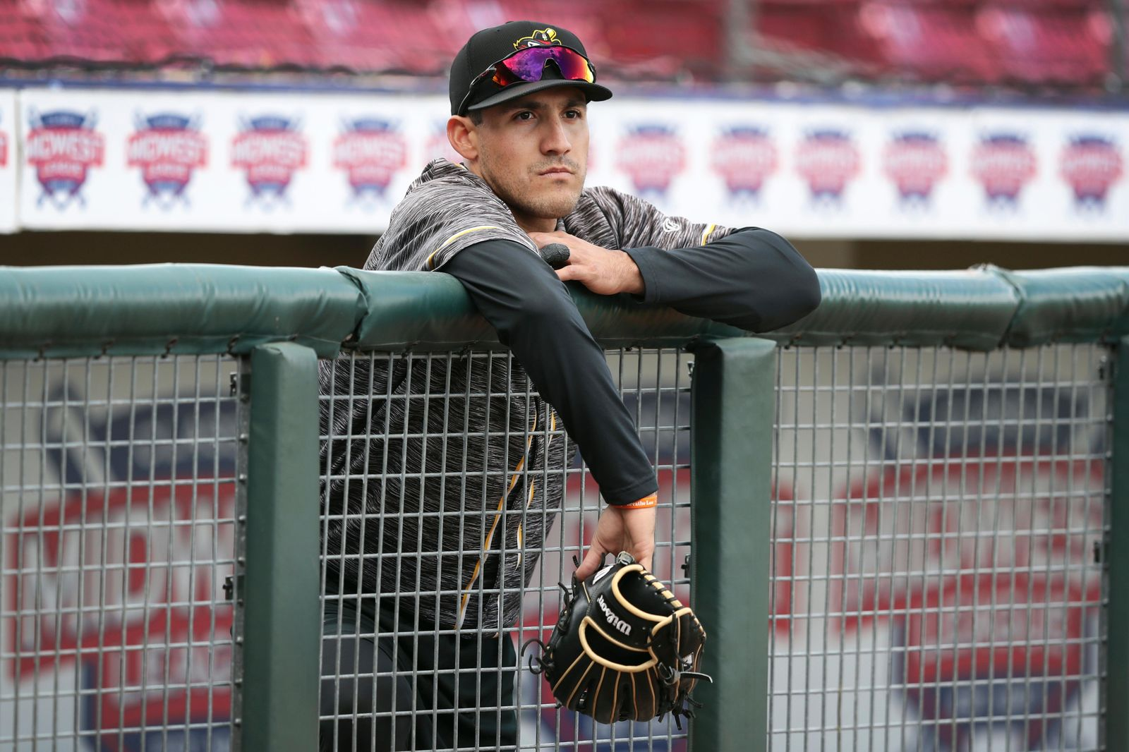 In this Monday, May 13, 2019 photo, Quad Cities River Bandits outfielder Alex McKenna stands in the dugout before a Class-A Midwest League baseball game against the Cedar Rapids Kernels in Cedar Rapids, Iowa. Quad Cities will play at least 40 of their first 43 games away from their home stadium Modern Woodmen Park because of water issues caused by flooding from the nearby Mississippi River. (AP Photo/Charlie Neibergall)