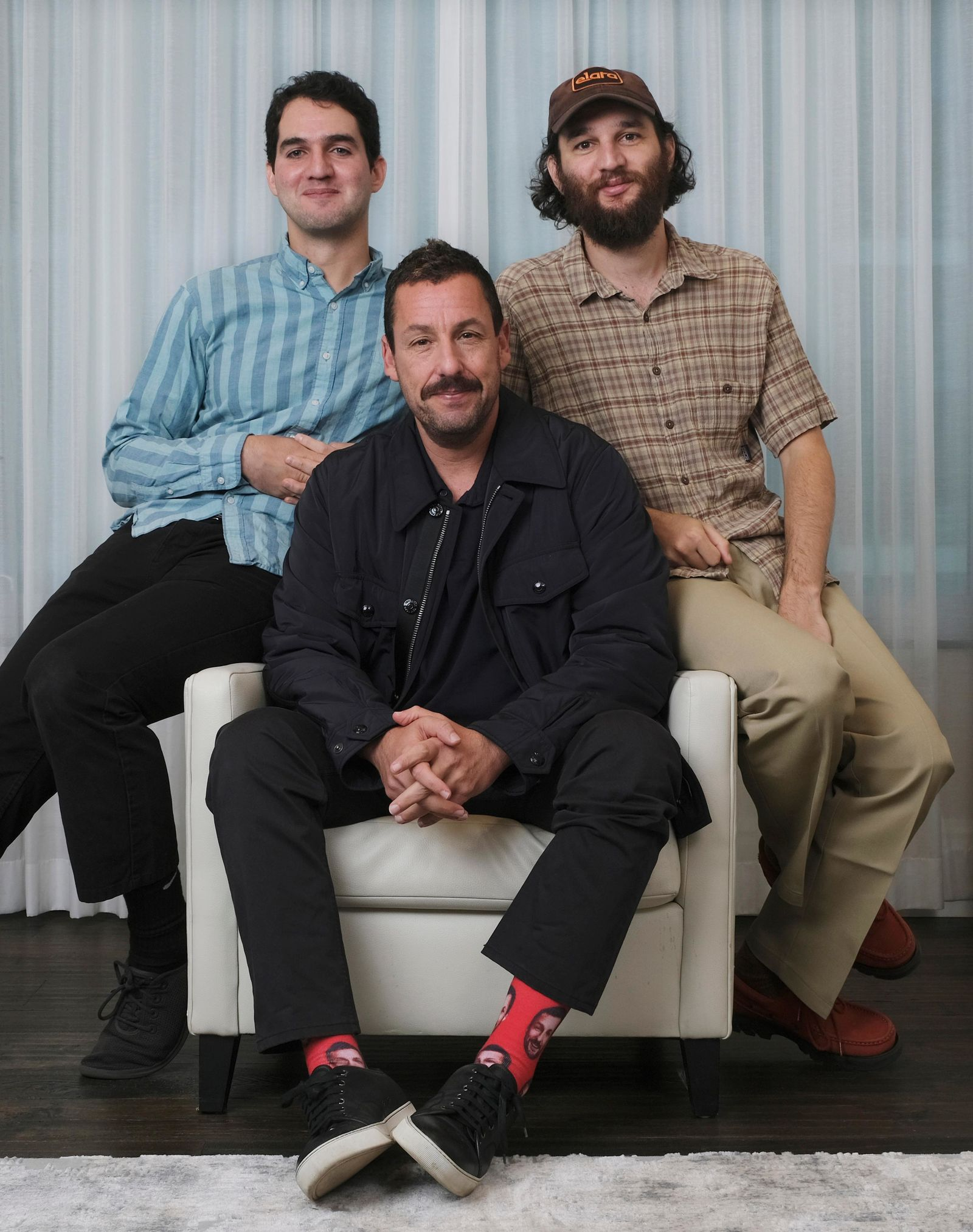 "This Sept. 9, 2019 photo shows Adam Sandler, center, star of the film ""Uncut Gems,"" posing for a portrait with co-directors Benny Safdie, left, and his brother Josh at the St. Regis Hotel during the Toronto International Film Festival in Toronto. (Photo by Chris Pizzello/Invision/AP)"