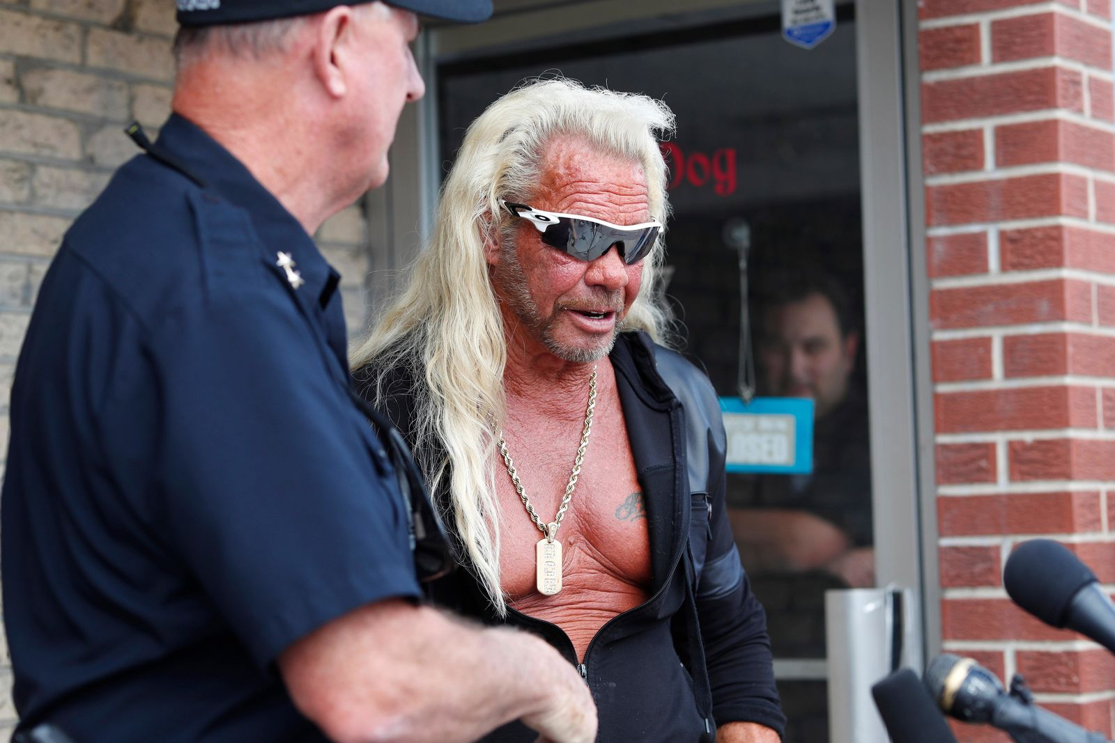 "Duane ""Dog the Bounty Hunter"" Chapman, right greets John Mackey, chief of police of Edgewater, Colo., during a news conference outside Chapman's storefront that was burglarized Friday, Aug. 2, 2019, in Edgewater, Colo. (AP Photo/David Zalubowski)"