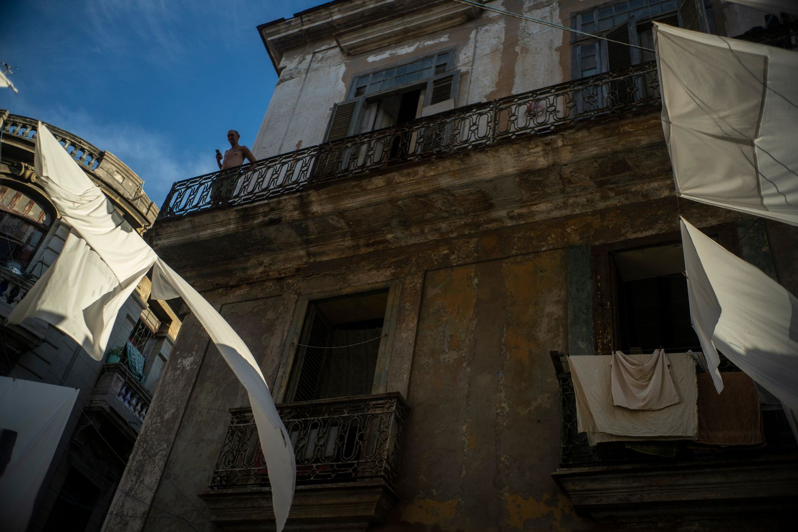 In this Nov. 9, 2019 photo, a man stands on the balcony of his home amid drying sheets in Havana, Cuba. The city of Havana will celebrate its 500th anniversary on Nov. 16. (AP Photo/Ramon Espinosa)