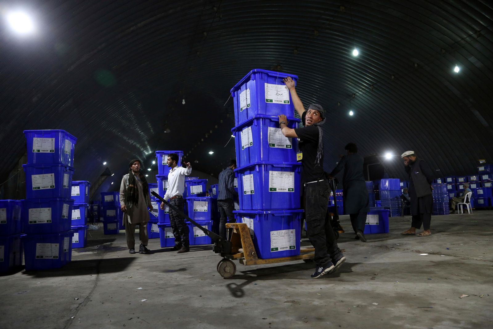 Election commission workers stack ballot boxes in preparation for the presidential election scheduled for Sept. 28, at