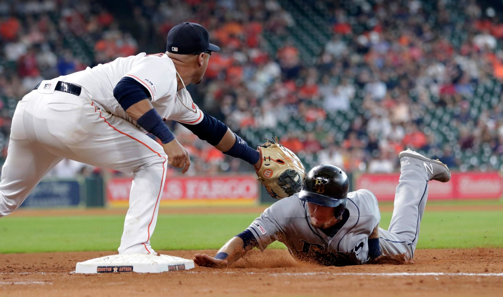 Houston Astros first baseman Yuli Gurriel, left, waits for the throw as Tampa Bay Rays' Matt Duffy, right, dives back to first base during the seventh inning of a baseball game Thursday, Aug. 29, 2019, in Houston. (AP Photo/Michael Wyke)