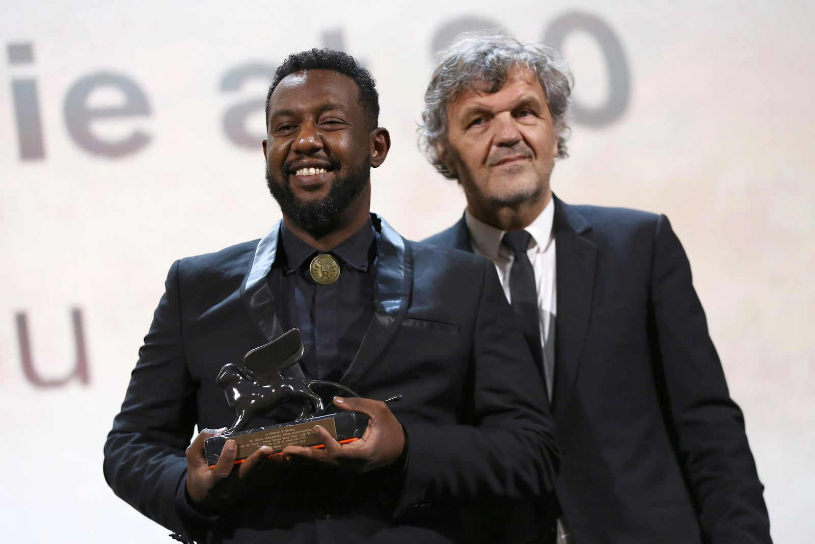 Director Amjad Abu Alala, left, holds the Luigi De Laurentiis Venice Award for a Debut Film for the film 'You Will Die At 20', presented by jury member Emir Kustirica at the closing ceremony of the 76th edition of the Venice Film Festival, Venice, Italy, Saturday, Sept. 7, 2019. (Photo by Joel C Ryan/Invision/AP)