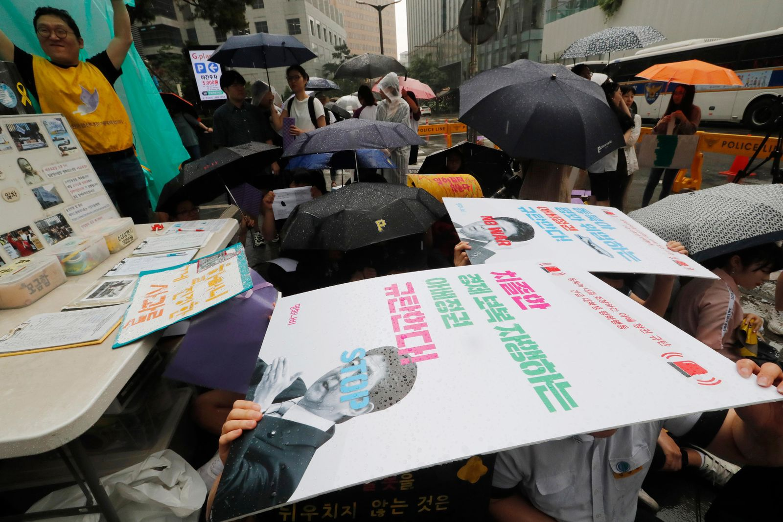 "Protesters hold their banners in the rain during a rally demanding full compensation and an apology for wartime sex slaves from Japanese government in front of the Japanese Embassy in Seoul, Wednesday, July 17, 2019. In his strongest comments yet on a growing trade dispute, South Korean President Moon Jae-in urged Japan on Monday to lift recently tightened controls on high-tech exports to South Korea, which he said threaten to shatter the countries' economic cooperation and could damage Japan more than South Korea. The signs read: ""Denounce, Abe's government."" (AP Photo/Ahn Young-joon)"