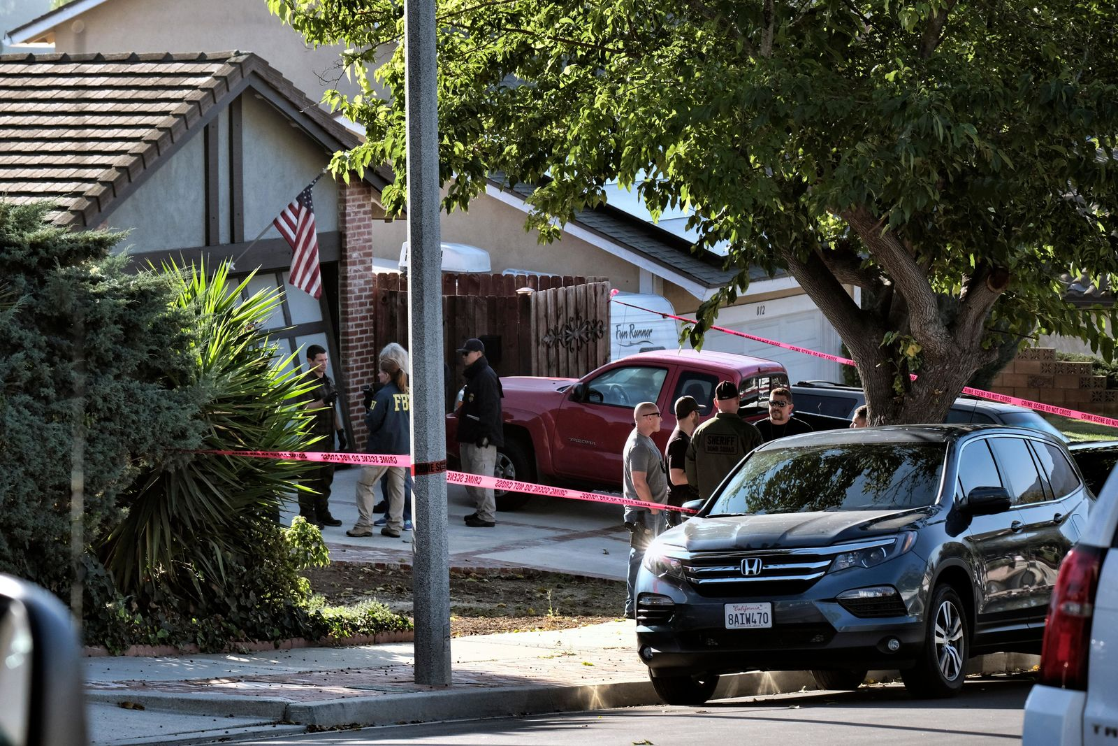 Ventura County Sheriff's deputies and FBI investigators stand outside the house of shooting suspect David Ian Long in Newbury Park, Calif., on Thursday, Nov. 8, 2018. (AP Photo/Richard Vogel)