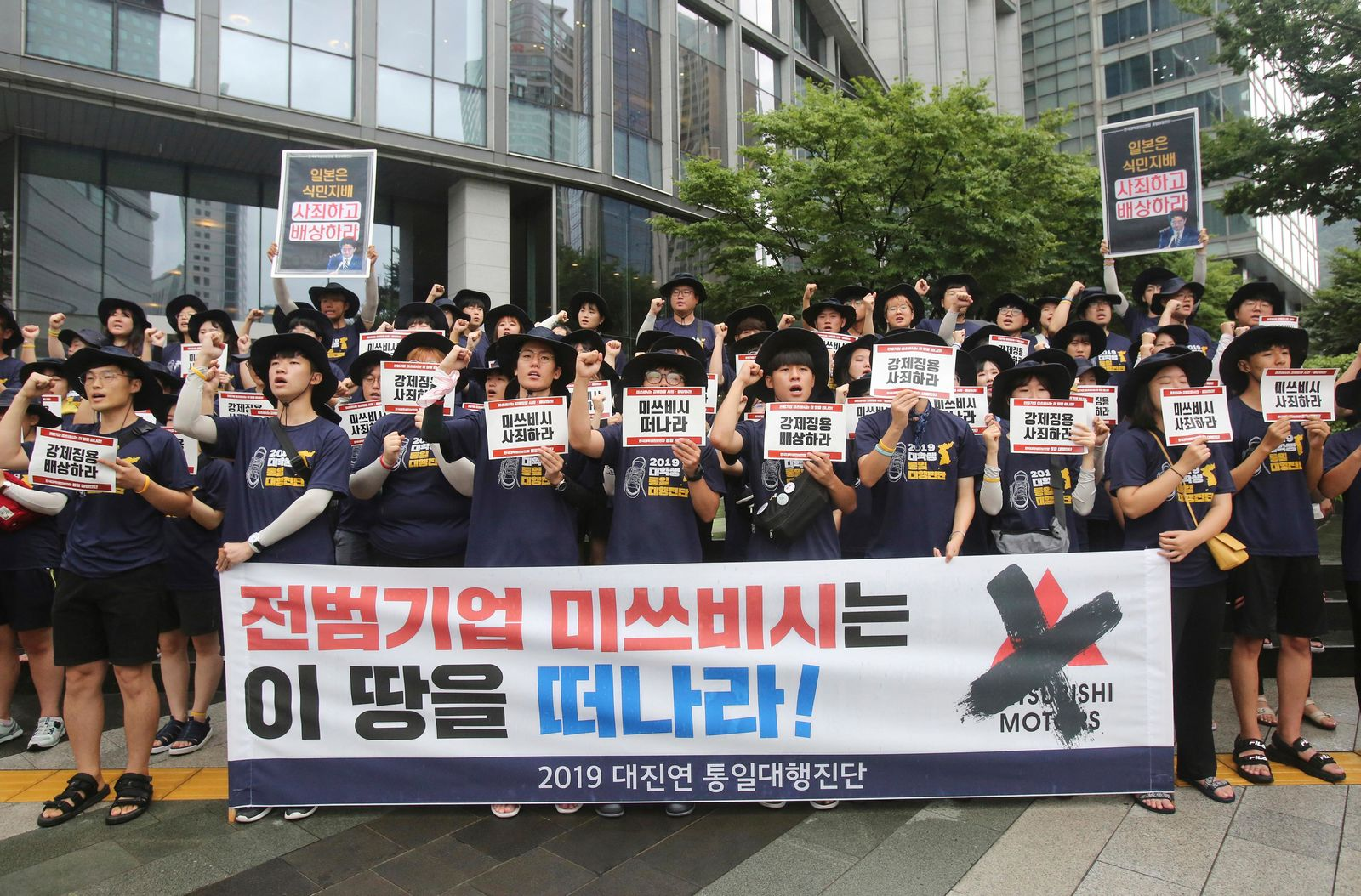 South Korean college students shout slogans during a rally to denounce Japan's new trade restrictions on South Korea in front of the office of Mitsubishi Corp. in Seoul, South Korea, Wednesday, Aug. 7, 2019. (AP Photo/Ahn Young-joon)