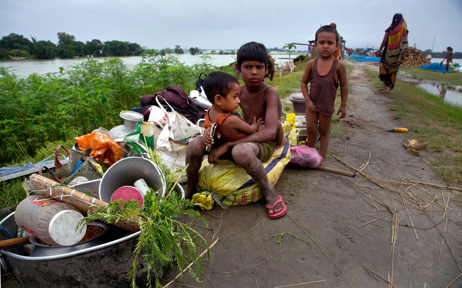 Flood affected children sit near their belongings on an embankment in Pabhokathi village east of Gauhati India, Monday, July 15, 2019. (AP Photo/Anupam Nath)