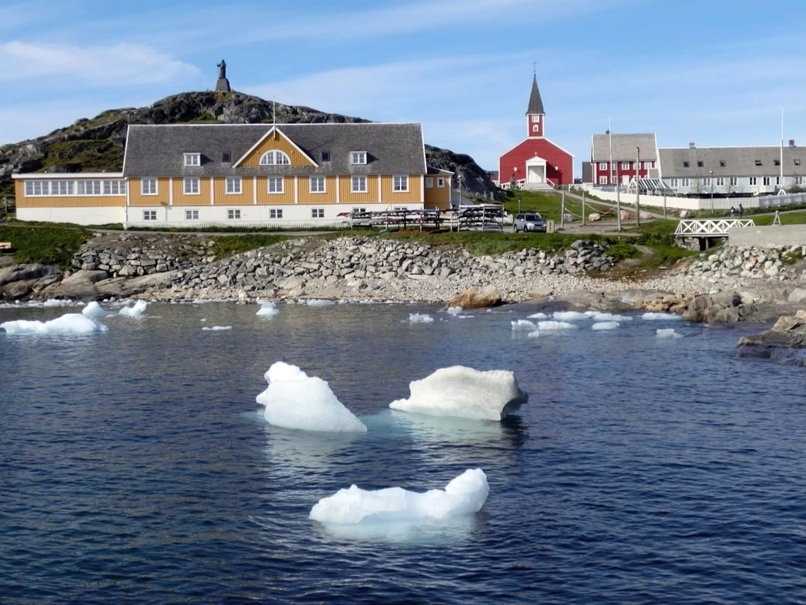 In this image taken on June 13, 2019 small pieces of ice float in the water off the shore in Nuuk, Greenland. (AP Photo/Sandy Virgo)