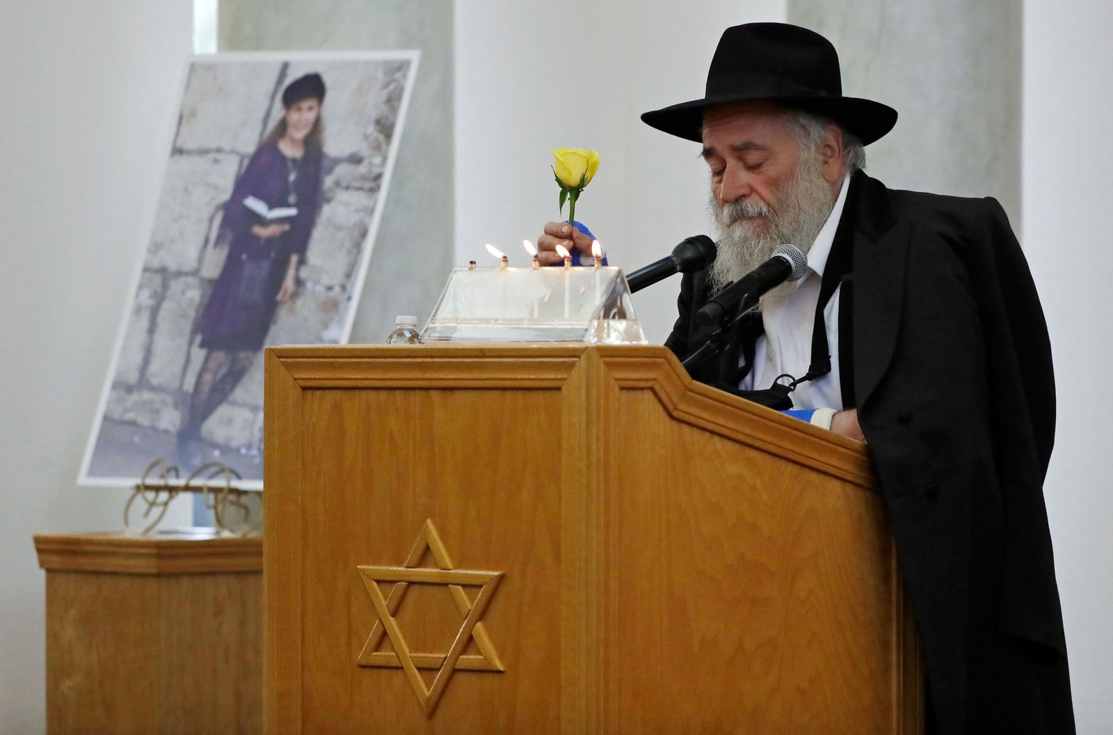 FILE - In this April 29, 2019 file photo, Yisroel Goldstein, Rabbi of Chabad of Poway, holds a yellow rose as he speaks at the funeral for Lori Kaye, who is pictured at left, in Poway, Calif. (AP Photo/Gregory Bull, File)