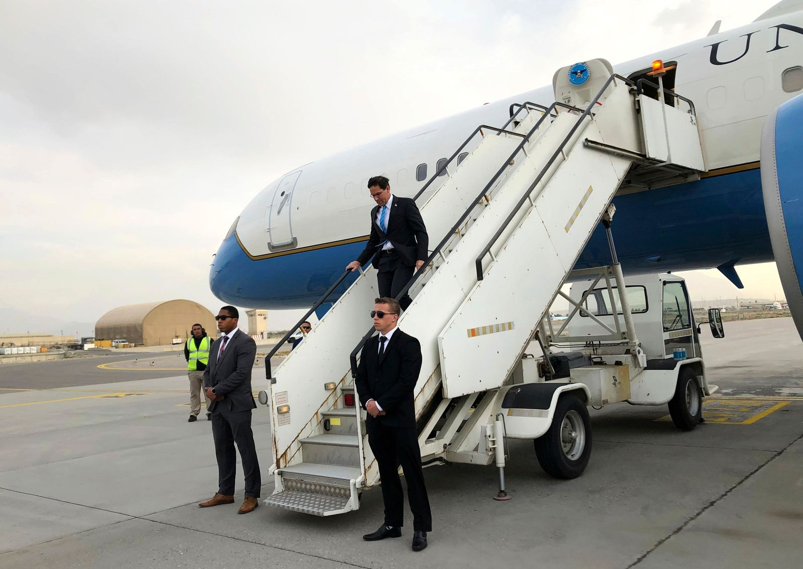 U.S. Defense Secretary Mark Esper, center, arrives in Kabul, Afghanistan, Sunday, Oct. 20, 2019. Esper arrived Sunday in Afghanistan, where stalled peace talks with the Taliban and persistent violent attacks by the insurgent group and Islamic State militants have complicated the Trump administration's pledge to withdraw more than 5,000 American troops. He told reporters traveling with him that he believes the U.S. can reduce its force in Afghanistan without hurting the counterterrorism fight against al-Qaida and the Islamic State group. (AP Photo/Lolita C. Balbor)