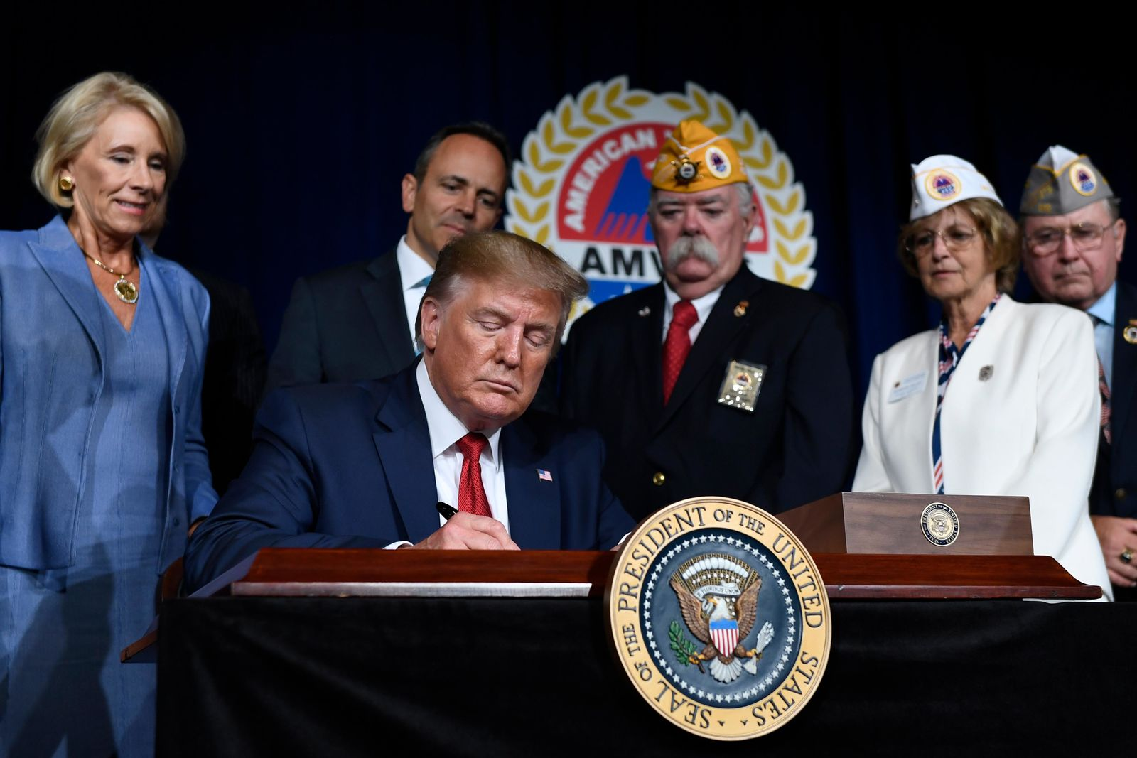 President Donald Trump signs a presidential memorandum that discharges the federal student loan debt of totally and permanently disabled veterans following his speech at the American Veterans (AMVETS) 75th National Convention in Louisville, Ky., Wednesday, Aug. 21, 2019. (AP Photo/Susan Walsh)