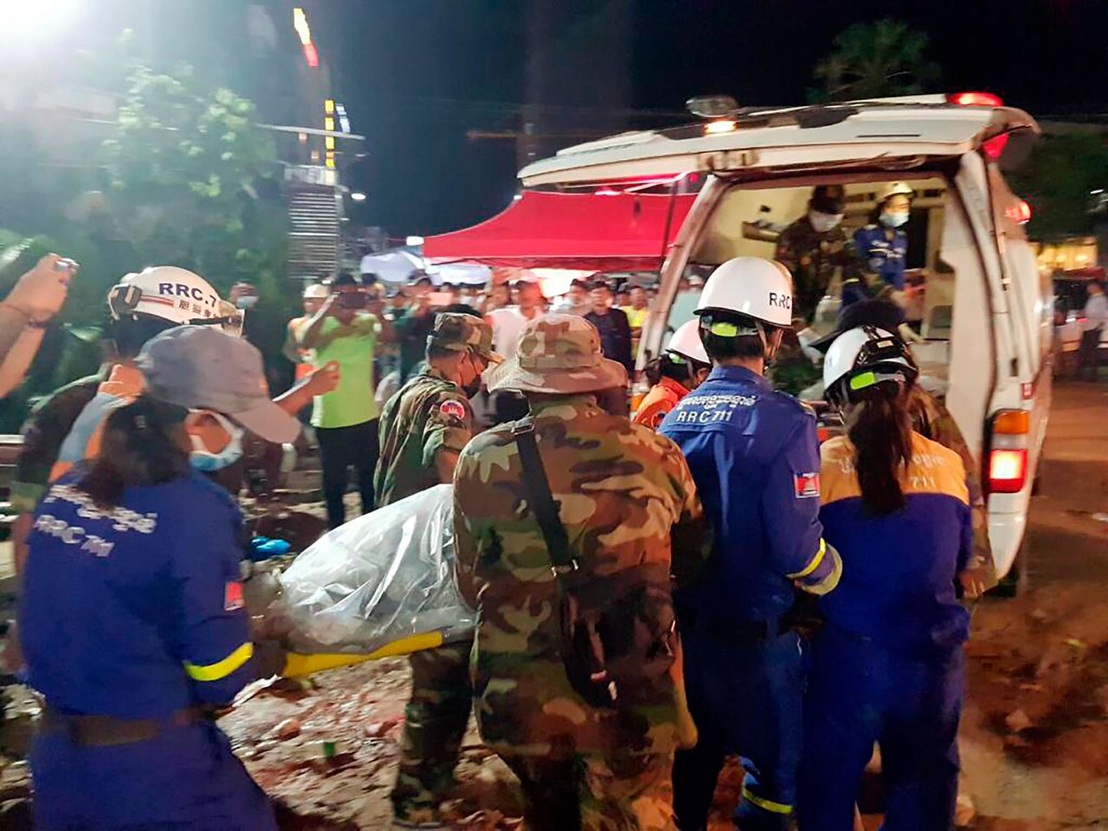 In this Sunday, June 23, 2019, photo provided by Preah Sihanouk provincial authorities, rescuers enter a victim body onto an ambulance at a site of a collapse in Preah Sihanouk province, Cambodia.{ } (Preah Sihanouk provincial authorities via AP)