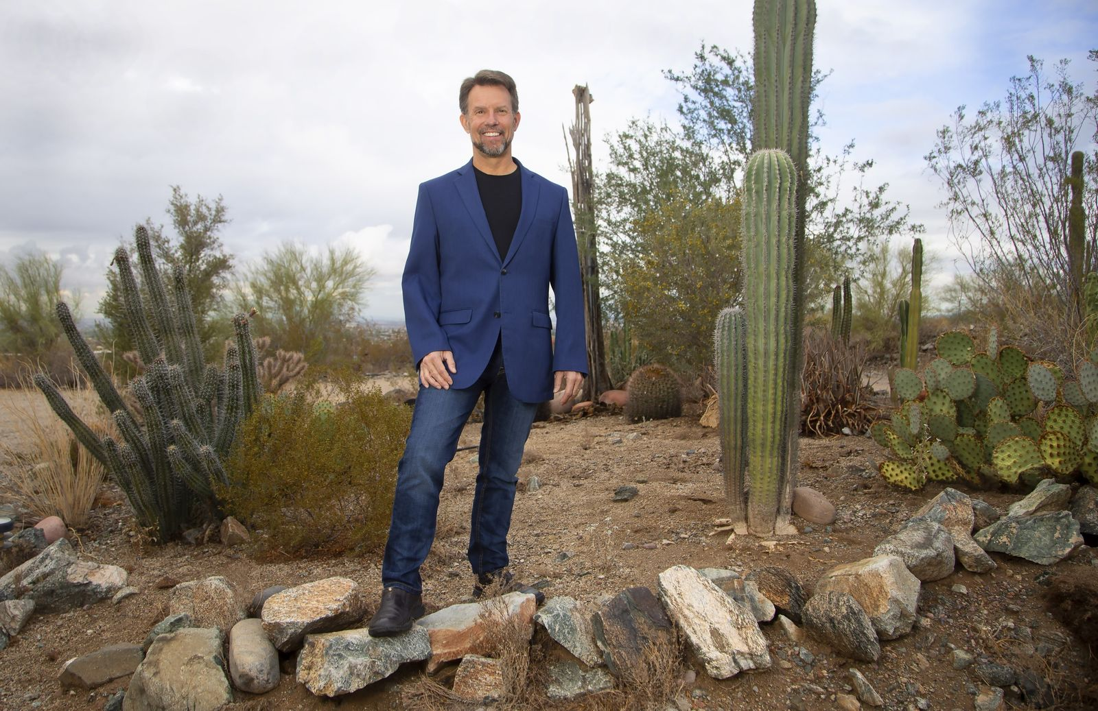Geodesist Michael Dennis, NOAA's National Geodetic Survey, stands in the foothills of South Mountain Thursday, Nov. 21, 2019, in Laveen, Ariz. The small difference between the U.S. survey foot and the international foot caused trouble in planning for high speed rail in California, and created a mess for bridge work between Oregon, which uses the international foot, and Washington, which uses the U.S. one, he says. (AP Photo/Ross D. Franklin)