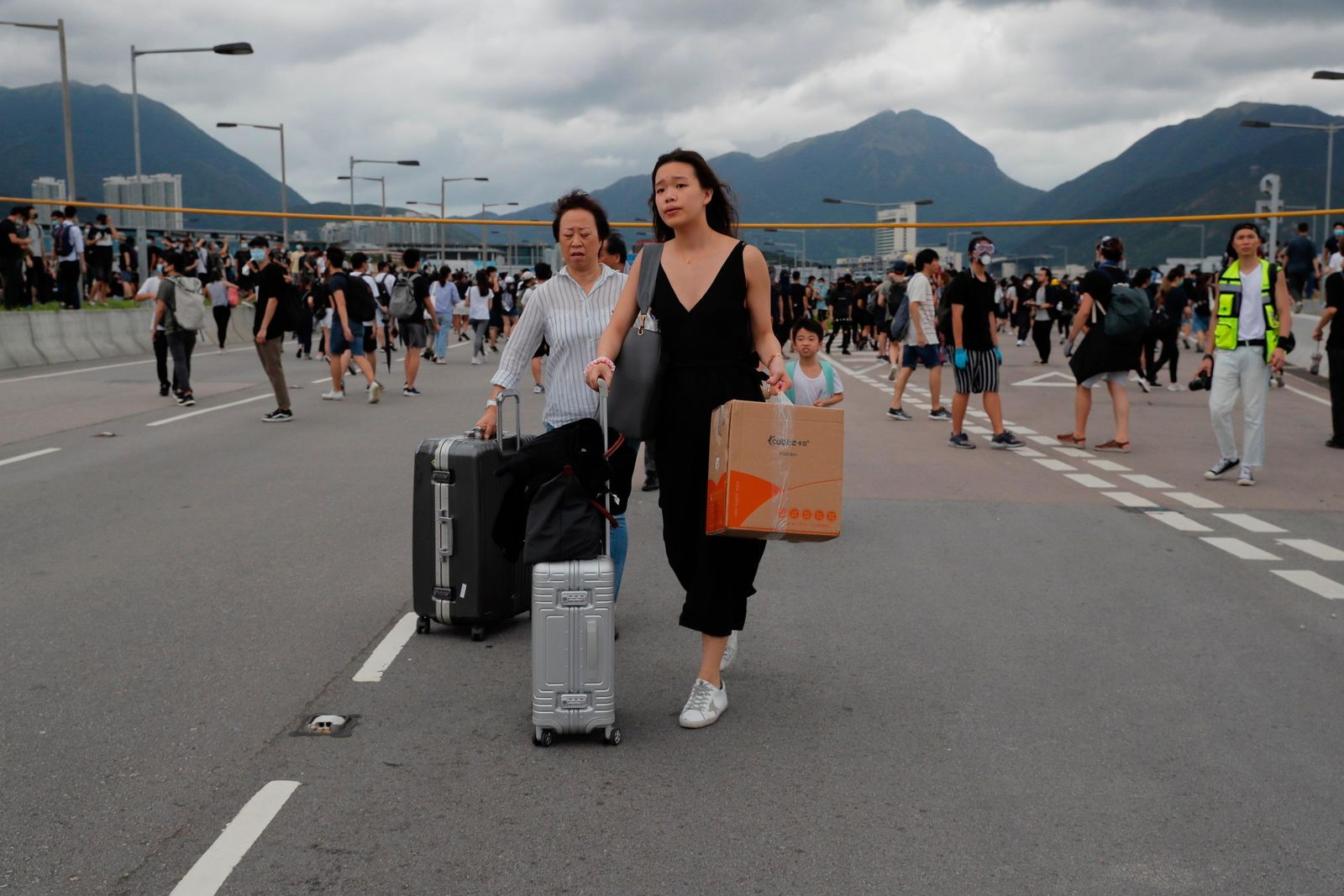 Passengers walk to airport as pro-democracy protestors blocked a road outside the airport in Hong Kong, Sunday, Sept.1, 2019.{ } (AP Photo/Kin Cheung)