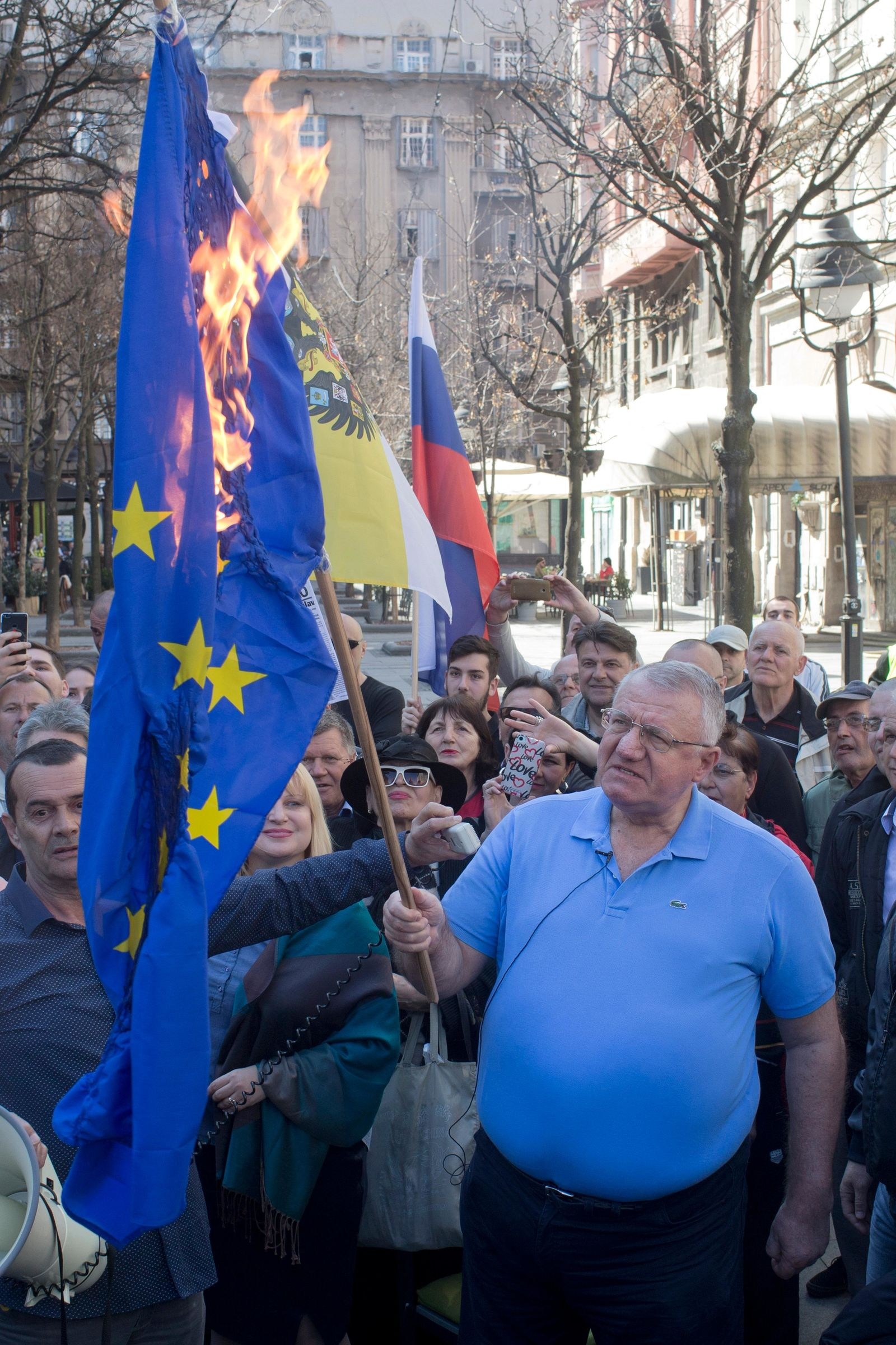 Vojislav Seselj, front, the leader of the ultranationalist Serbian Radical Party, holds a burning EU flag as he and others gather for a protest in Belgrade, Serbia, Sunday, March 24, 2019.{ } (AP Photo/Marko Drobnjakovic)