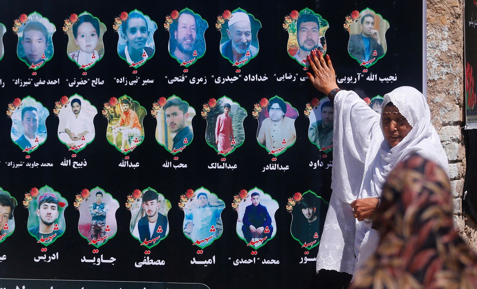 An Afghan woman cries as she touches a banner displaying photographs of victims of the Dubai City wedding hall bombing during a memorial service in Kabul, Afghanistan, Tuesday, Aug. 20, 2019. The deadly bombing at a wedding in Afghanistan's capital late last Saturday that killed dozens of people was a stark reminder that the war-weary country faces daily threats not only from the long-established Taliban but also from a brutal local affiliate of the Islamic State group, which claimed responsibility for the attack. (AP Photo/Rafiq Maqbool)