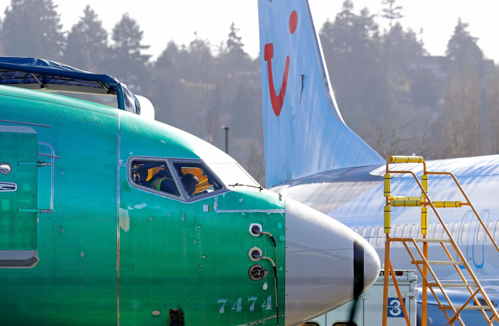 FILE- In this March 13, 2019, file photo people work in the flight deck of a Boeing 737 MAX 8 airplane being built for TUI Group parked next to another MAX 8 also designated for TUI at Boeing Co.'s Renton Assembly Plant in Renton, Wash.{ } (AP Photo/Ted S. Warren, file)