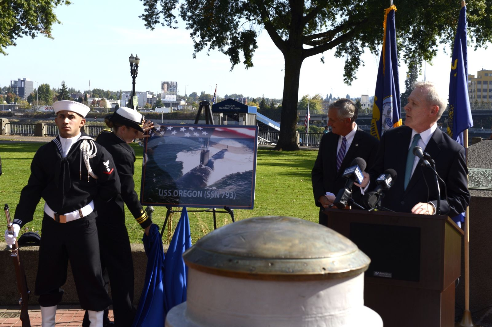 Secretary of the Navy (SECNAV) Ray Mabus unveils the future Virginia-class submarine USS Oregon (SSN 793) at the Battleship Oregon Memorial at Gov. Tom McCall Waterfront Park as Mayor of Portland Charlie Hales looks on. in October 2014. (U.S. Navy photo by Mass Communication Specialist 2nd Class Armando Gonzales/Released)