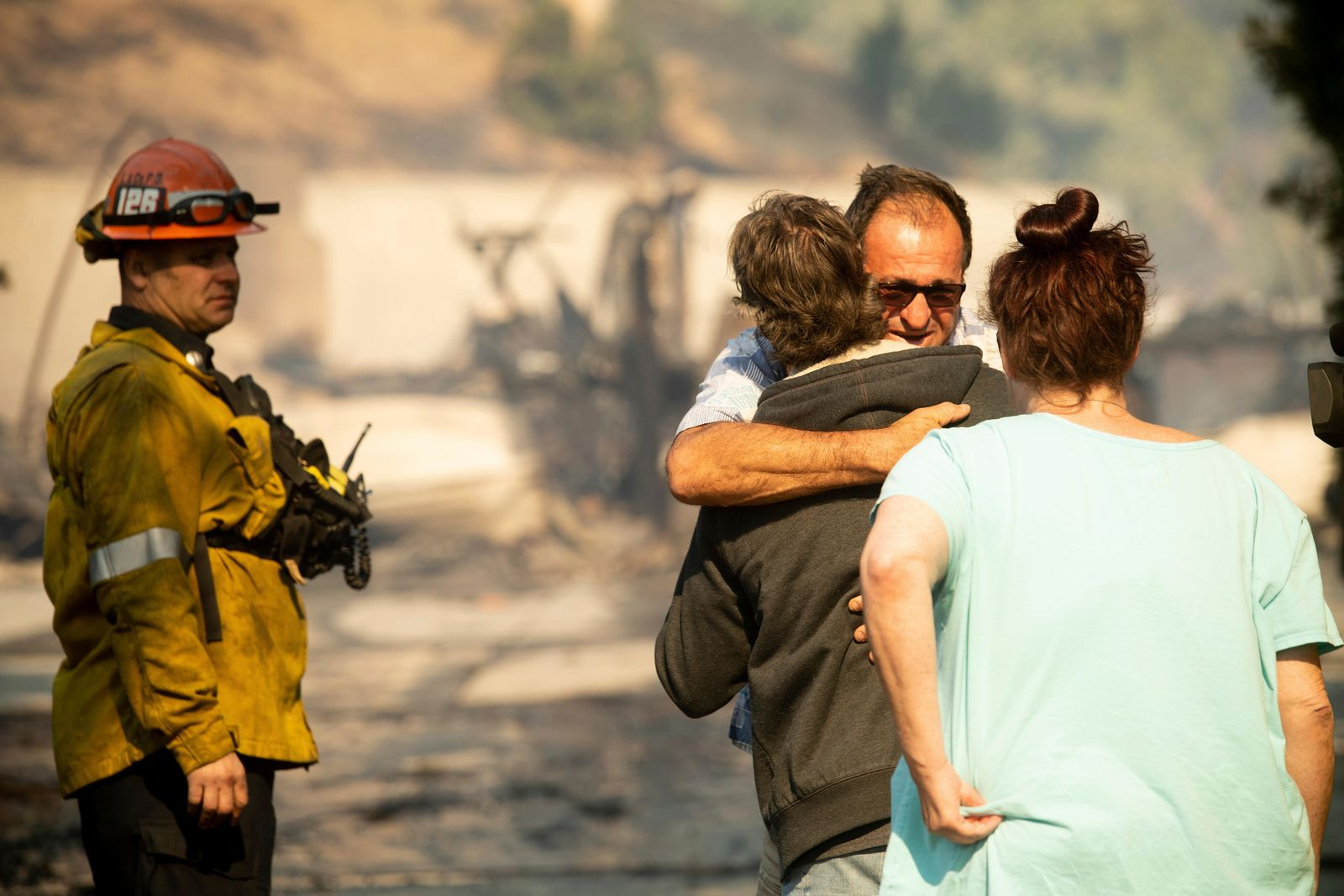 Eyed Jarjour comforts a neighbor who lost his Jolette Ave. home to the Saddleridge Fire on Friday, Oct. 11, 2019, in Granada Hills, Calif. (AP Photo/Noah Berger)
