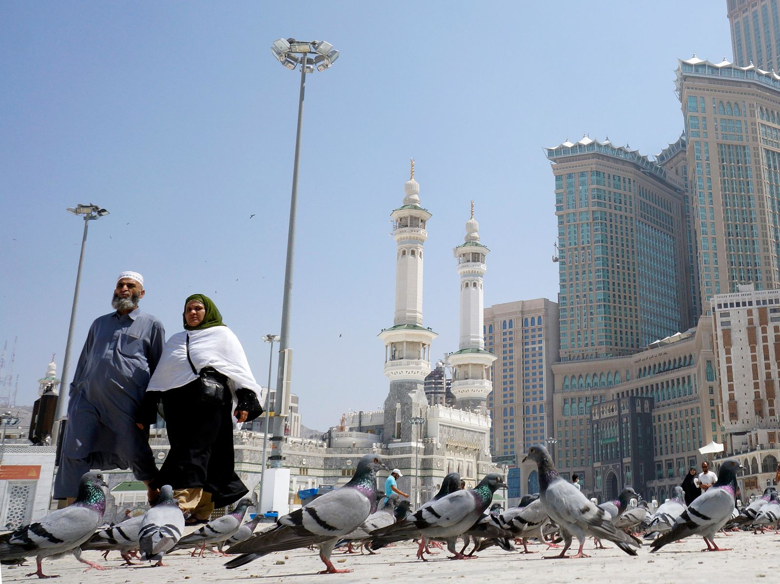 Muslim worshippers walk past pigeons after the noon prayers outside the Grand Mosque, in the Muslim holy city of Mecca, Saudi Arabia, Saturday, March 7, 2020. (AP Photo/Amr Nabil)