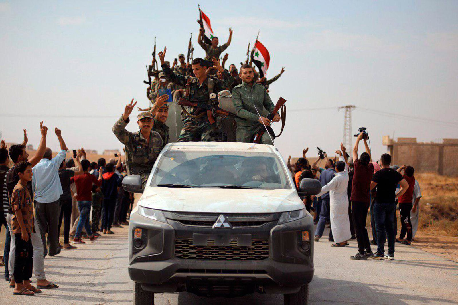In this photo released by the Syrian official news agency SANA, people welcome Syrian troops as they enter the town of Ein Issa, north of Raqqa, Syria, Monday, Oct 14, 2019.{ } (SANA via AP)
