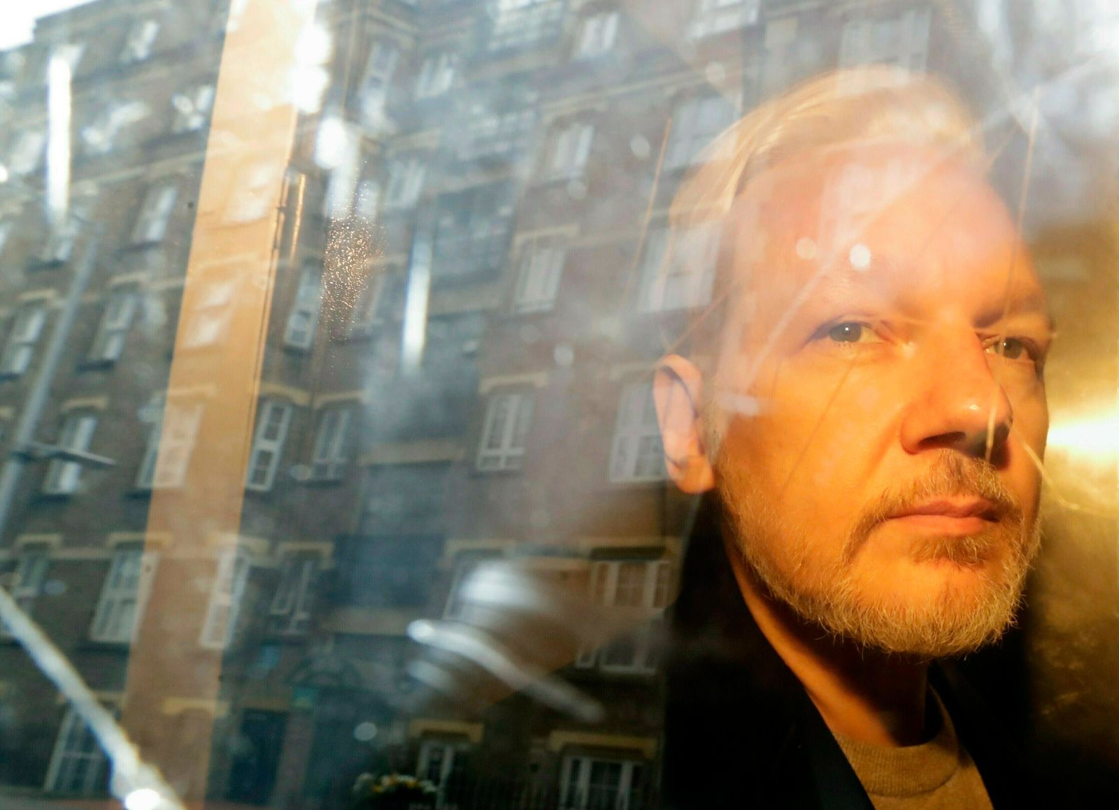FILE - In this Wednesday, May 1, 2019 file photo, buildings are reflected in the window as WikiLeaks founder Julian Assange is taken from court, where he appeared on charges of jumping British bail seven years ago, in London. (AP Photo/Matt Dunham, File)