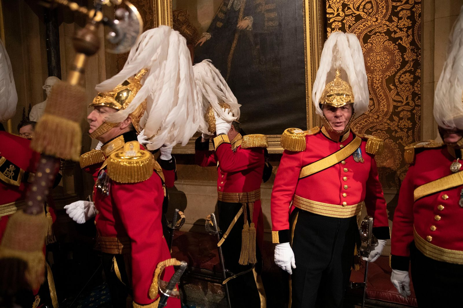 Members of the Honourable Corps of Gentlemen at Arms get ready to line-up in the Norman Porch at the Palace of Westminster and the Houses of Parliament at the State Opening of Parliament ceremony in London, Monday, Oct. 14, 2019. (AP Photo/Matt Dunham, Pool)
