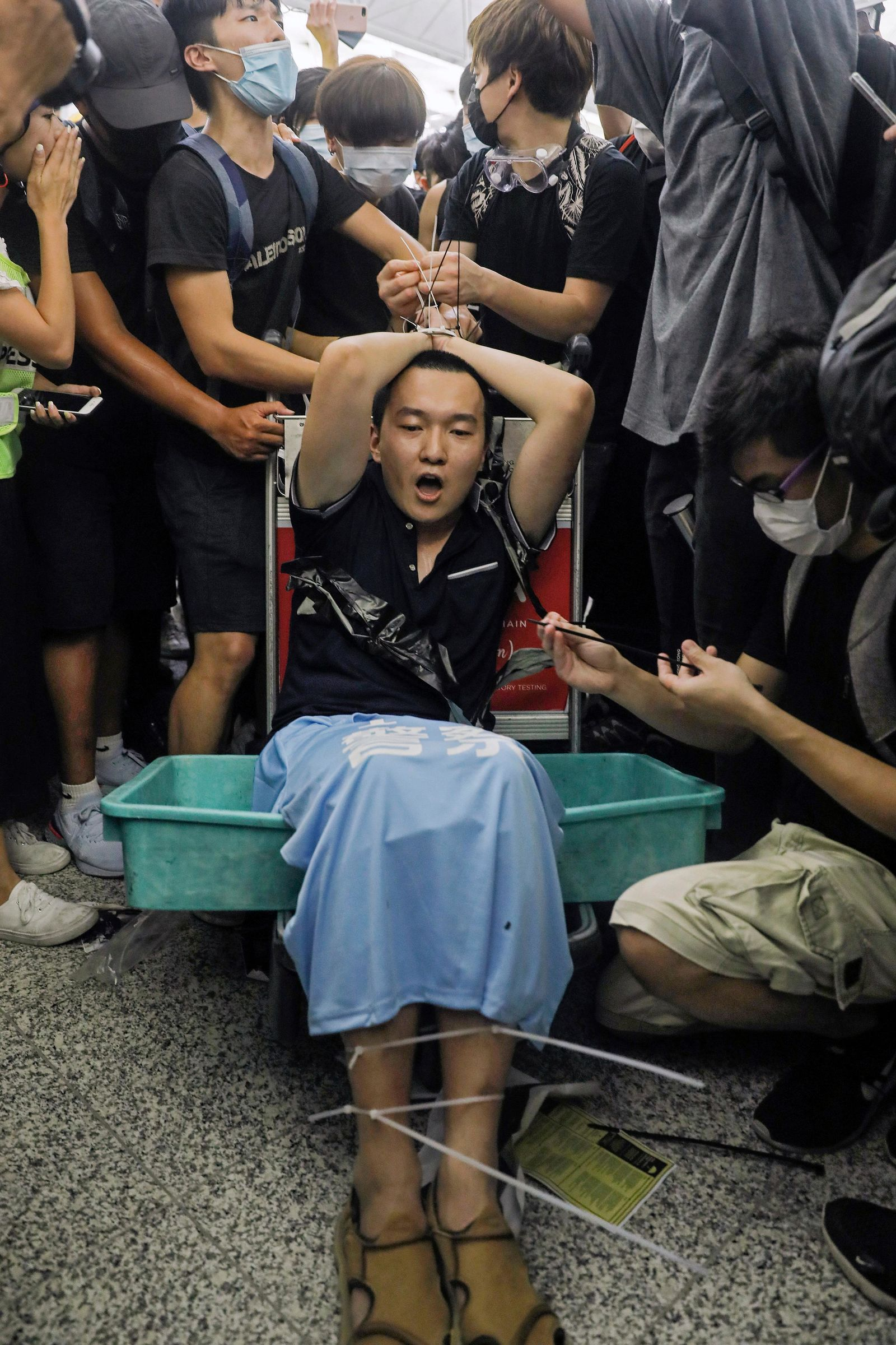 Protesters restrain a man on a luggage trolley, who protesters claimed was a Chinese undercover agent during a demonstration at the Airport in Hong Kong, Tuesday, Aug. 13, 2019. Riot police clashed with pro-democracy protesters at Hong Kong's airport late Tuesday night, a chaotic end to a second day of demonstrations that caused mass flight cancellations at the Chinese city's busy transport hub. (AP Photo/Vincent Yu)
