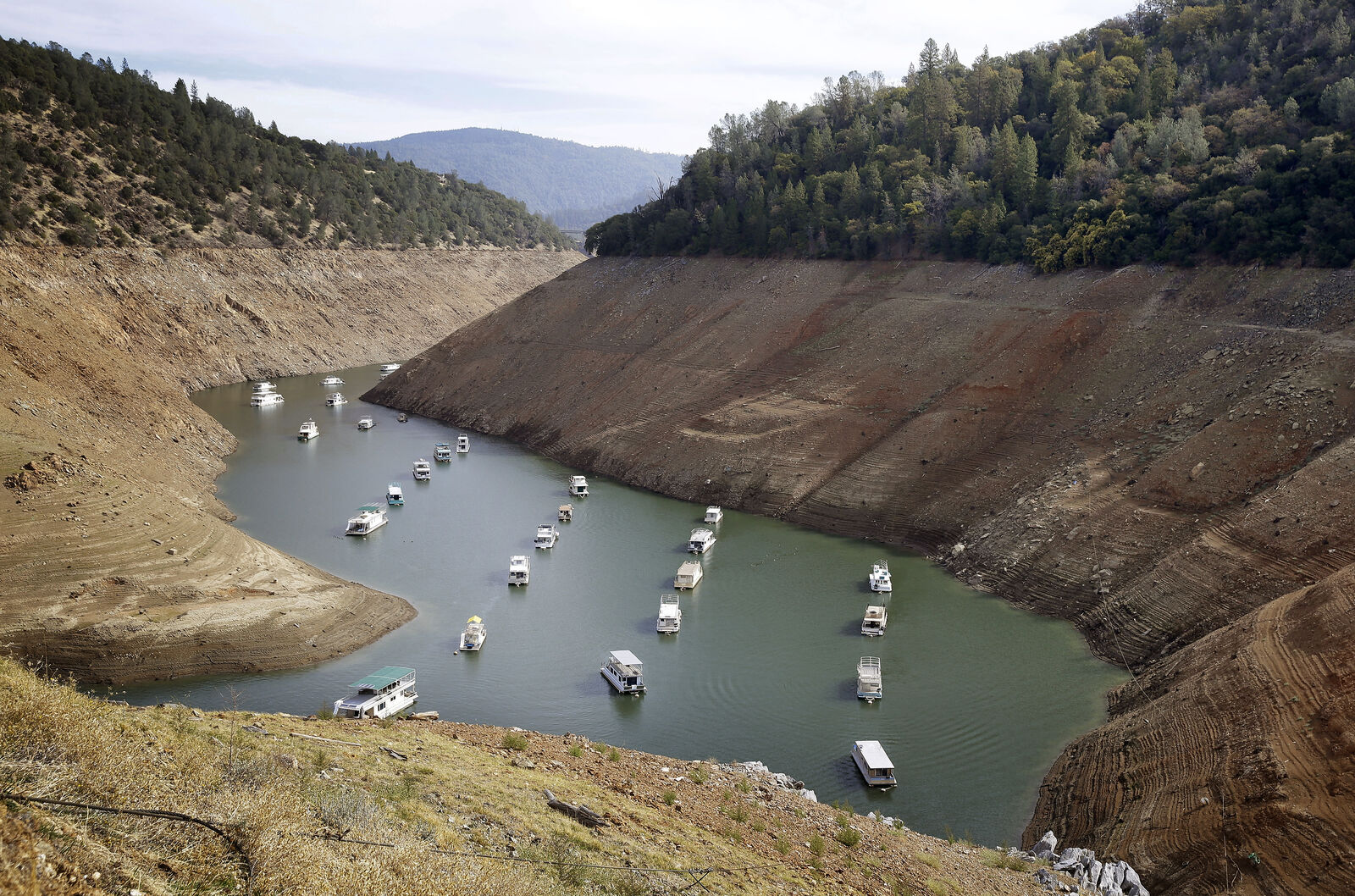 FILE - In this Oct. 30, 2014, file photo, houseboats float in the drought-lowered waters of Oroville Lake near Oroville, Calif. (AP Photo/Rich Pedroncelli, File)