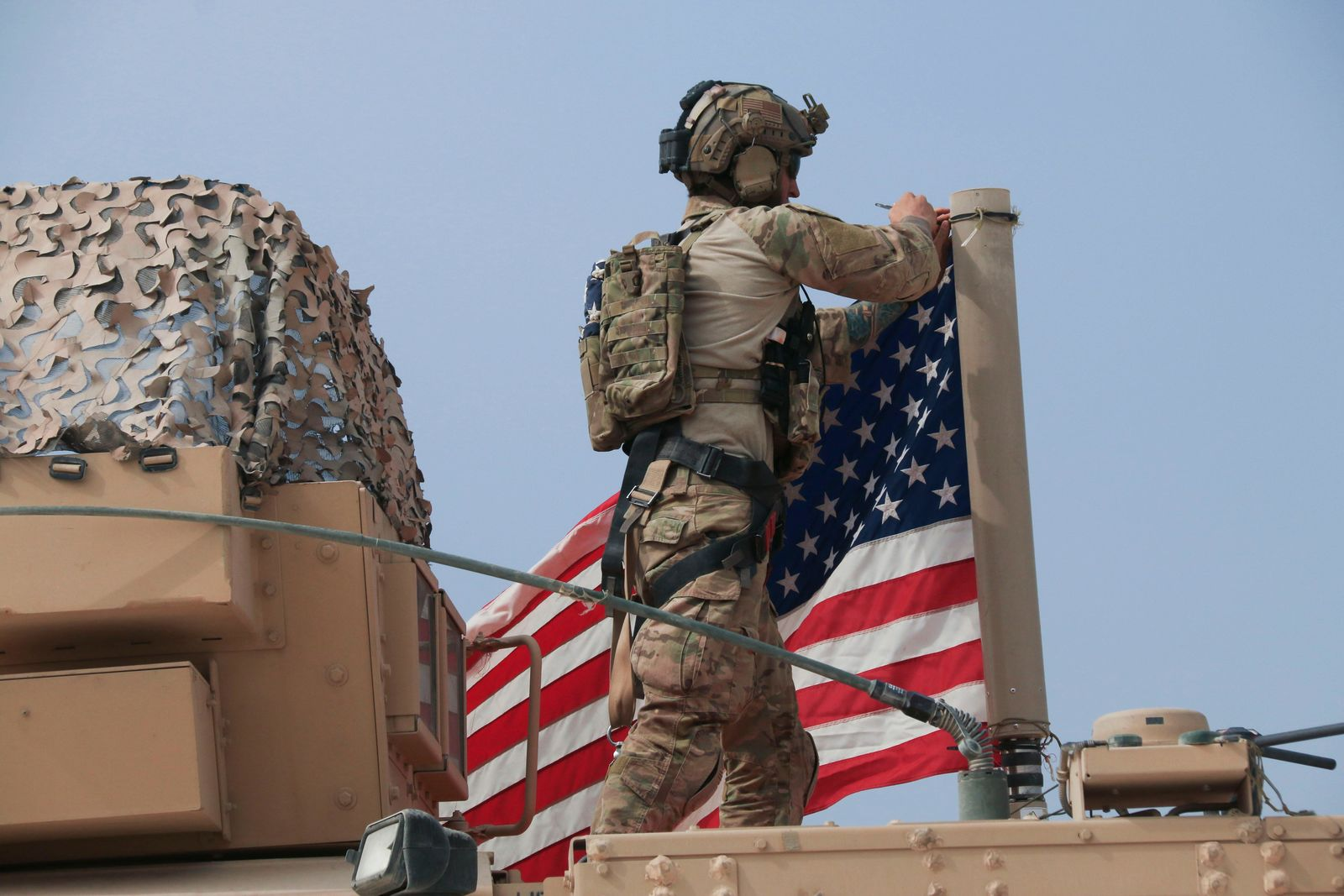 American soldier mount the U.S. flag on a vehicle near the town of Tel Tamr, north Syria, Sunday, Oct. 20, 2019.{ } (AP Photo/Baderkhan Ahmad)