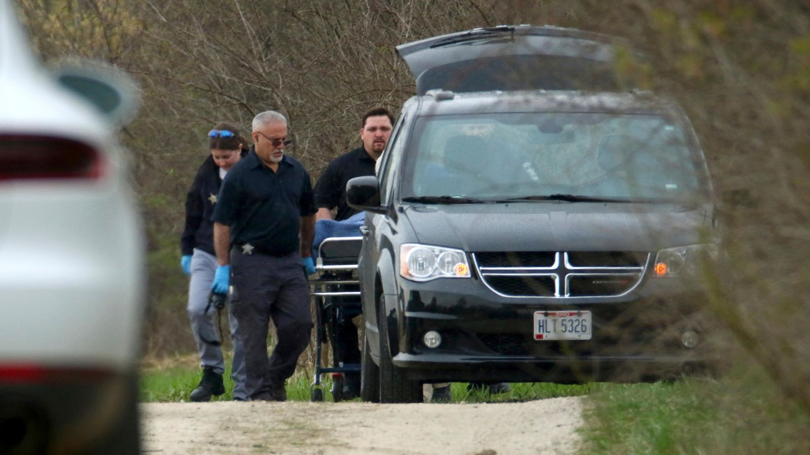 "McHenry County Coroner investigators load the body of 5-year-old Andrew ""AJ"" Freund into a minivan at a wooded area off Dean Street Wednesday, April 24, 2019, in Woodstock, Ill. The boy's parents have been charged with his murder. (John J. Kim/Chicago Tribune via AP)"