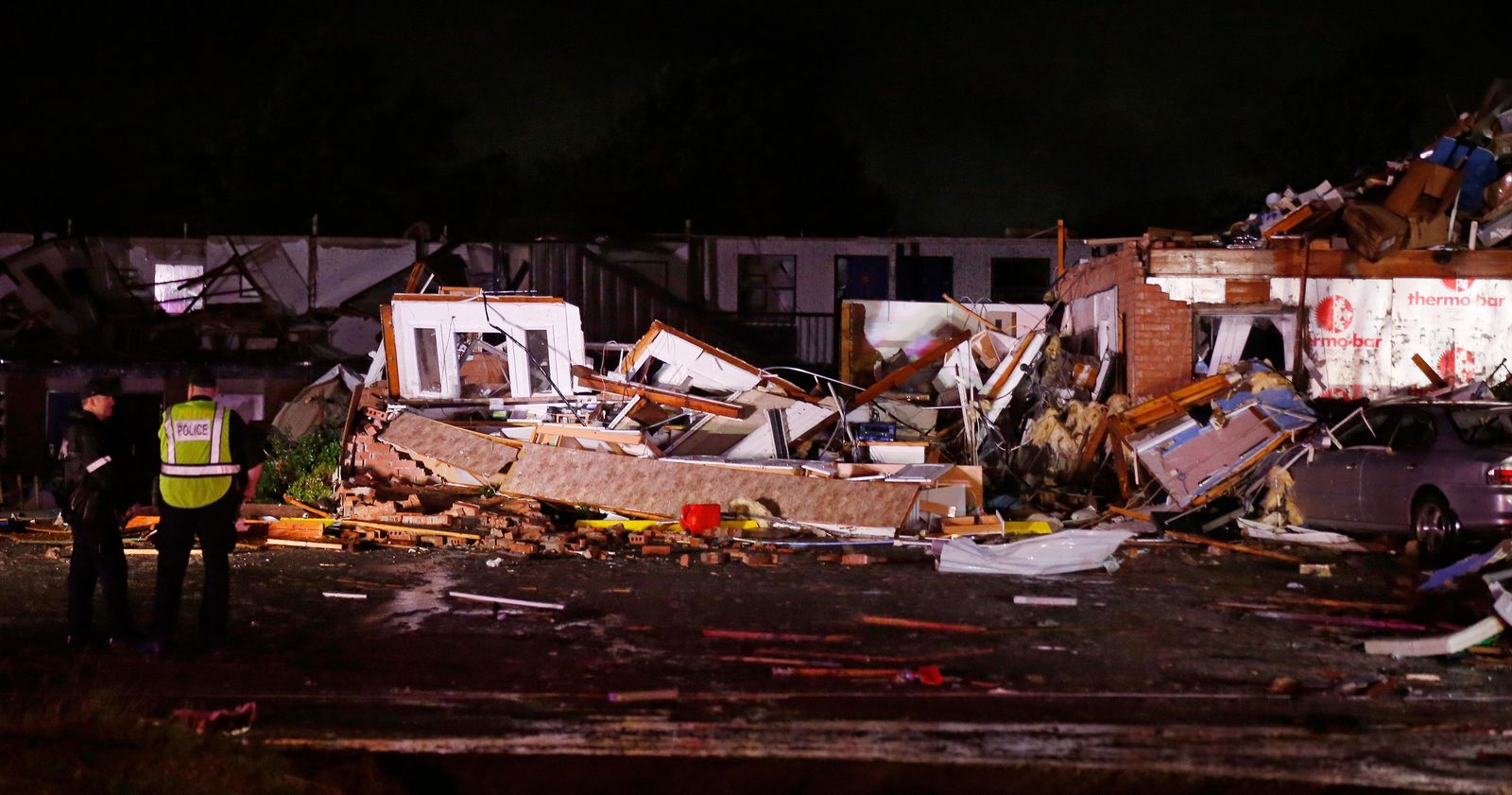Police stand at the ruins of a hotel in El Reno, Okla., Sunday, May 26, 2019, following a likely tornado touchdown late Saturday night. (AP Photo/Sue Ogrocki)