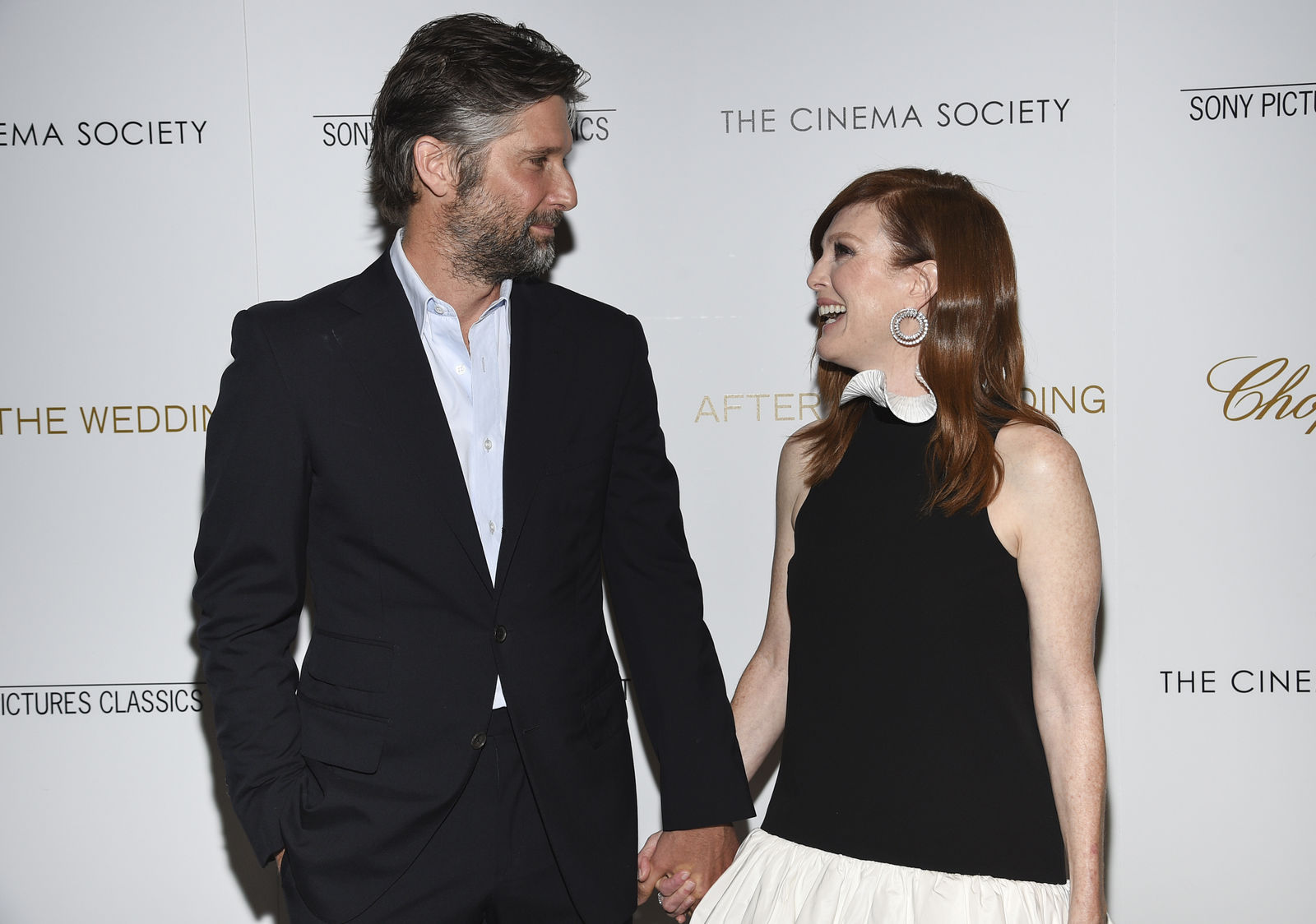 "FILE - In this Tuesday, Aug. 6, 2019 file photo, director Bart Freundlich, left, and wife, actor Julianne Moore, attend a special screening of ""After the Wedding"" in New York. (Photo by Evan Agostini/Invision/AP)"