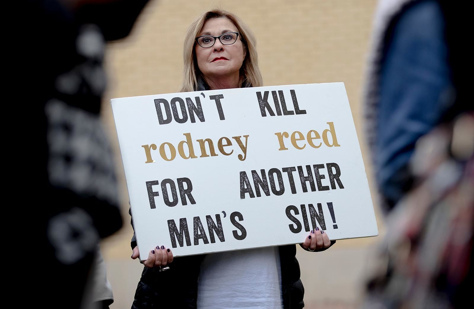 A woman holds a sign during a protest against the execution of Rodney Reed on Wednesday, Nov. 13, 2019, in Bastrop, Texas. Reed is scheduled to be executed Nov. 20, but a growing number of politicians and celebrities have joined calls to further examine Reed's case before his execution proceeds. (Nick Wagner/Austin American-Statesman via AP)