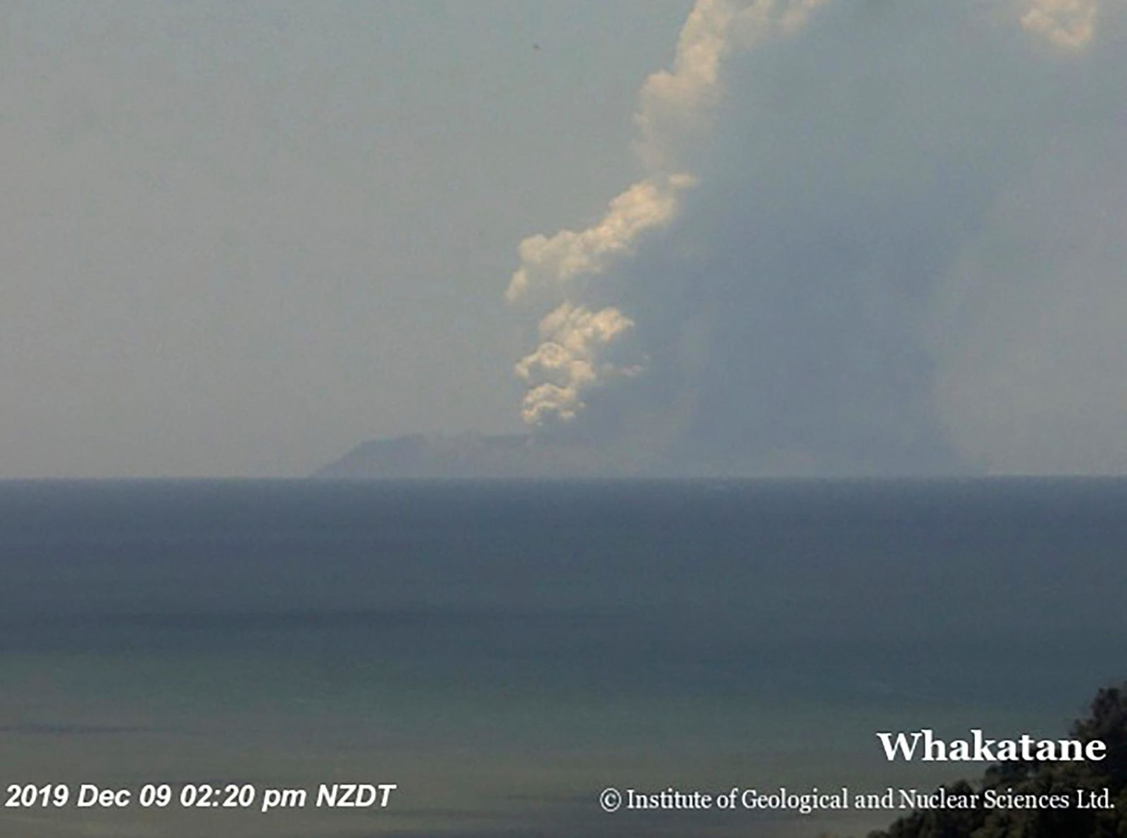 This image released by GNS Science, shows plumes of smoke from a volcanic eruption on White Island, seen from Whakatane, New Zealand Monday, Dec. 9, 2019.{ } (GNS Science via AP)