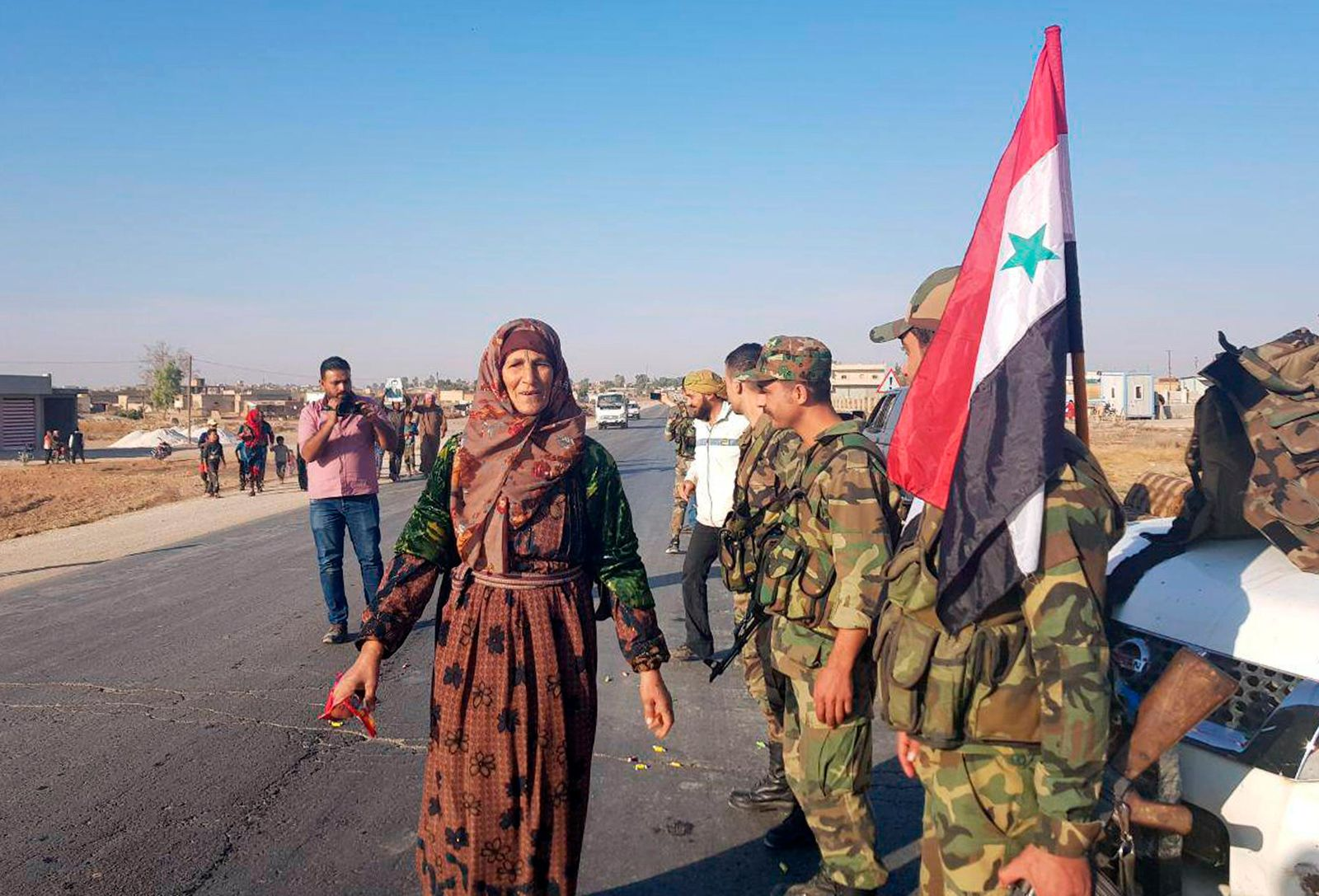 In this photo released by the Syrian official news agency SANA, residents welcome Syrian soldiers shortly after they entered the northern town of Tal Tamr on Monday, Oct 14, 2019.{ } (SANA via AP)
