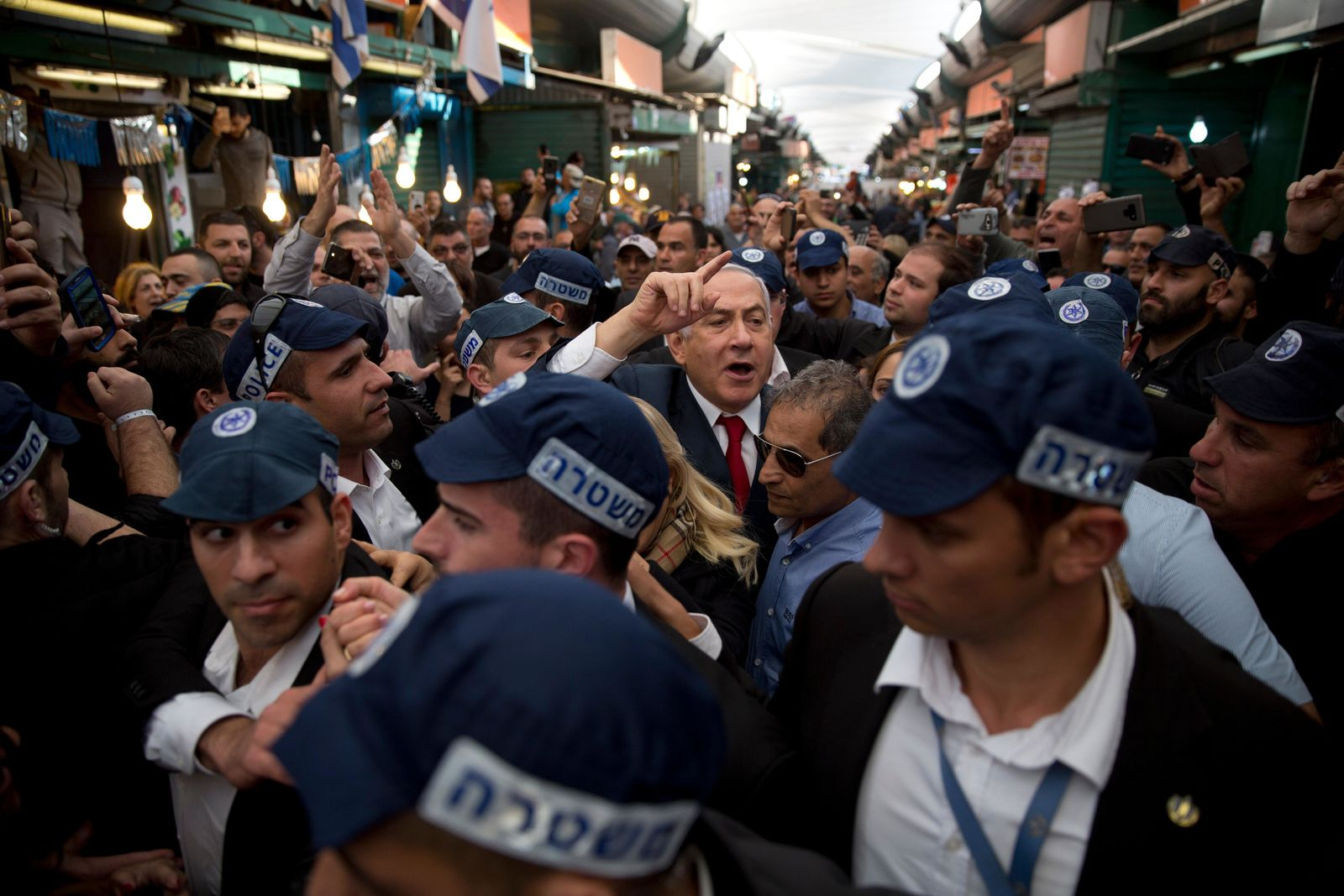 FILE - In this April 2, 2019 file photo, Israeli Prime Minister Benjamin Netanyahu, head of the Likud party, center, is escorted by security guards during a visit to the Ha'tikva market in Tel Aviv, Israel. (AP Photo/Oded Balilty, File)