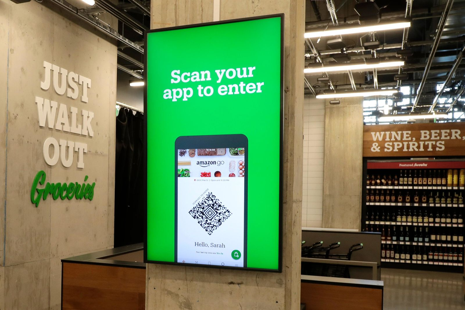 In this Feb. 21, 2020 photo, a sign tells shoppers how to check in when they enter an Amazon Go Grocery store set to open soon in Seattle's Capitol Hill neighborhood. (AP Photo/Ted S. Warren)