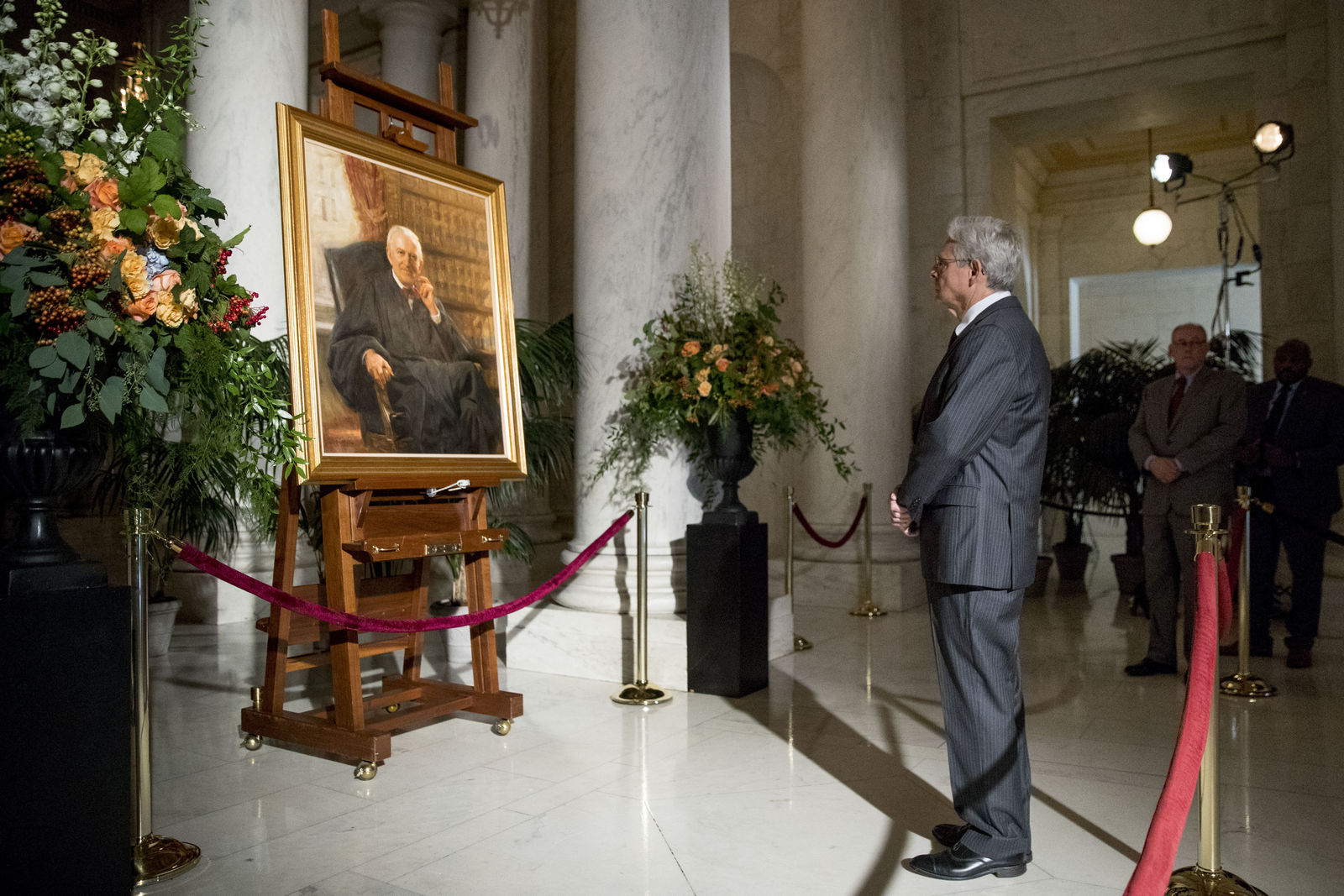 Former President Barack Obama's Supreme Court nominee Merrick Garland stops at a painting of the late Supreme Court Justice John Paul Stevens while paying his respects as Stevens lies in repose in the Great Hall of the Supreme Court in Washington, Monday, July 22, 2019. (AP Photo/Andrew Harnik)