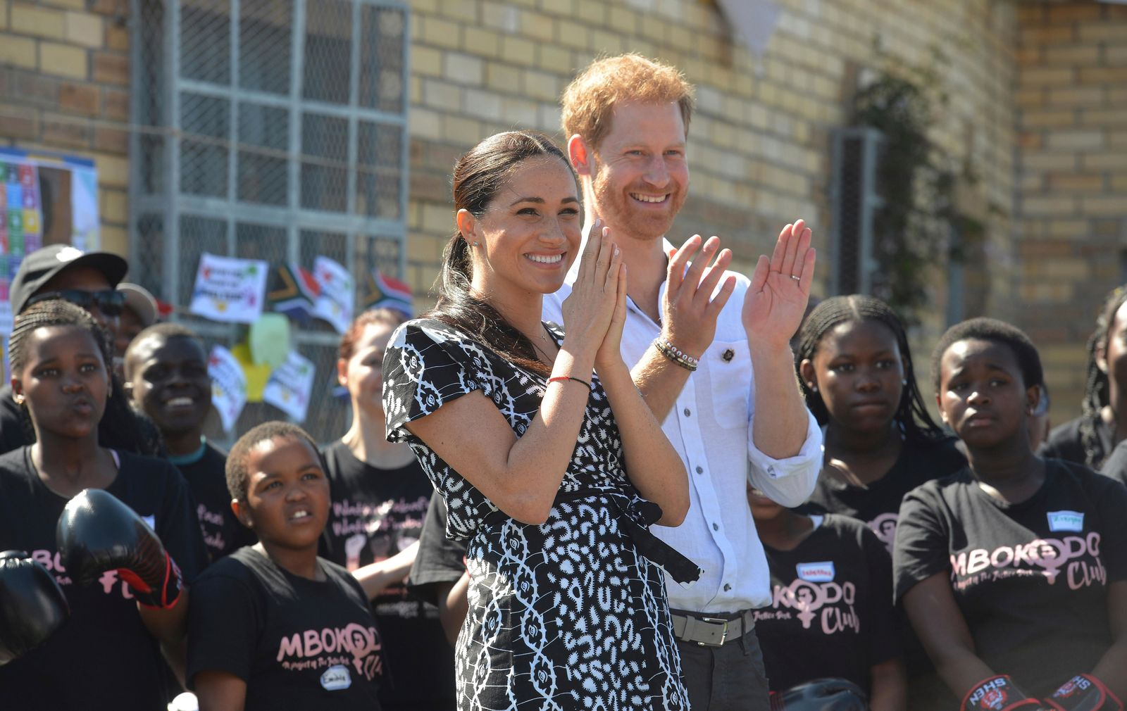 FILE - In this Monday, Sept, 23, 2019 file photo, Britain's Prince Harry and Meghan, Duchess of Sussex greet youths on a visit to the Nyanga Methodist Church in Cape Town, South Africa. (Courtney Africa/Pool via AP, File)