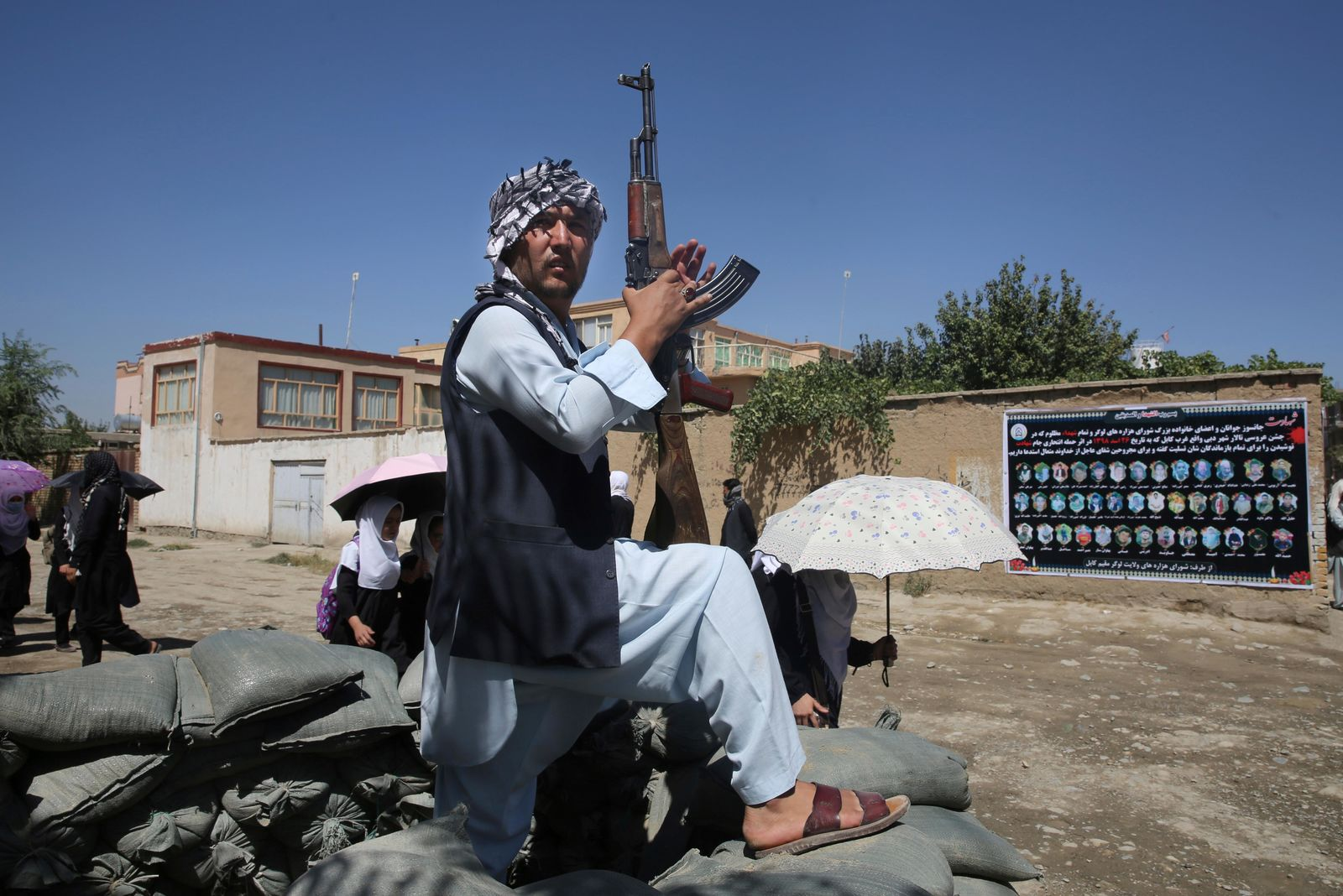 An Afghan volunteer stands guard outside a mosque during a memorial service for the victims of the Dubai City wedding hall bombing in Kabul, Afghanistan, Tuesday, Aug. 20, 2019. Hundreds of people have gathered in mosques in Afghanistan's capital for memorials for scores of people killed in a horrific suicide bombing at a Kabul wedding over the weekend. (AP Photo/Rafiq Maqbool)