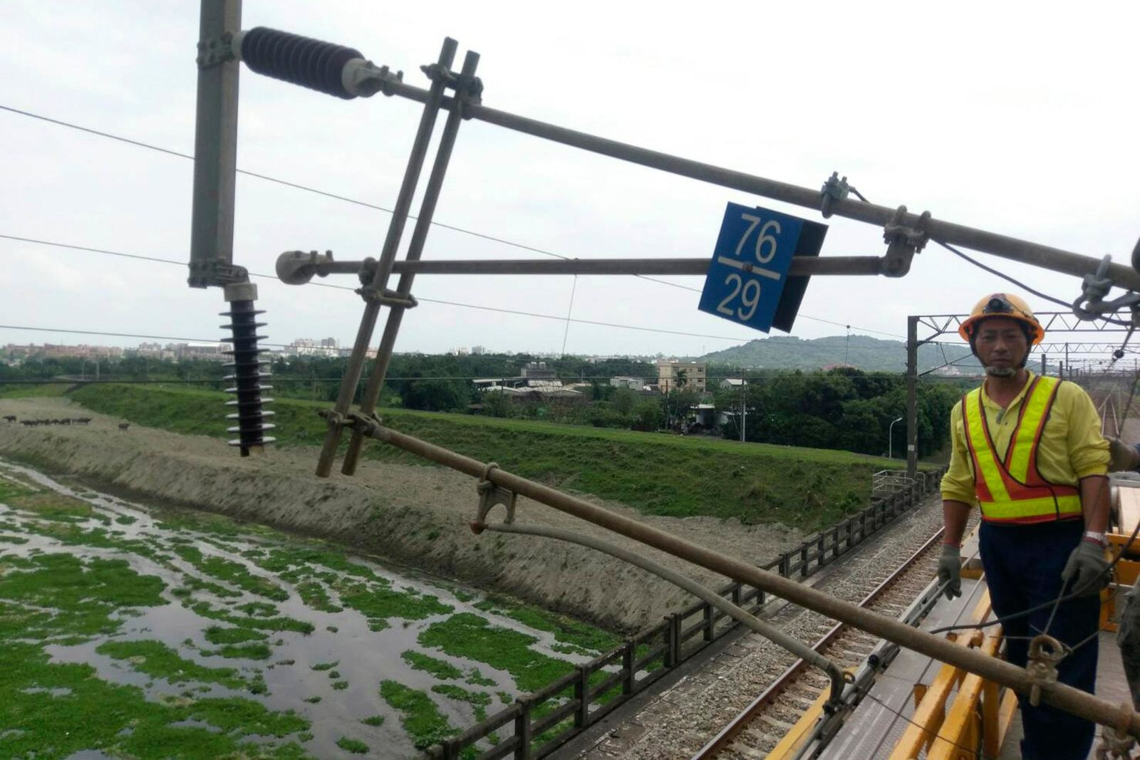 In this photo released by Taiwan Railways Administrations, a worker stands near damaged facilities for the railway line near Hualien in eastern Taiwan Thursday, April 18, 2019. (Taiwan Railways Administrations via AP)