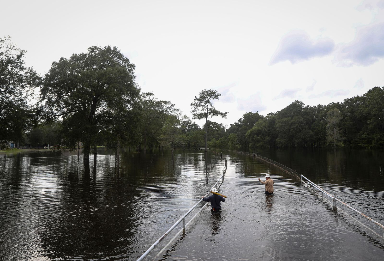 Mike Davis, left, and Trent Tipton, both line workers from Woodville, Texas, walk through floodwater to try to restore power for a customer on Friday, Sept. 20, 2019, in the Mauriceville, Texas, area. Floodwaters are starting to recede in most of the Houston area after the remnants of Tropical Storm Imelda flooded parts of Texas. ( Jon Shapley/Houston Chronicle via AP)