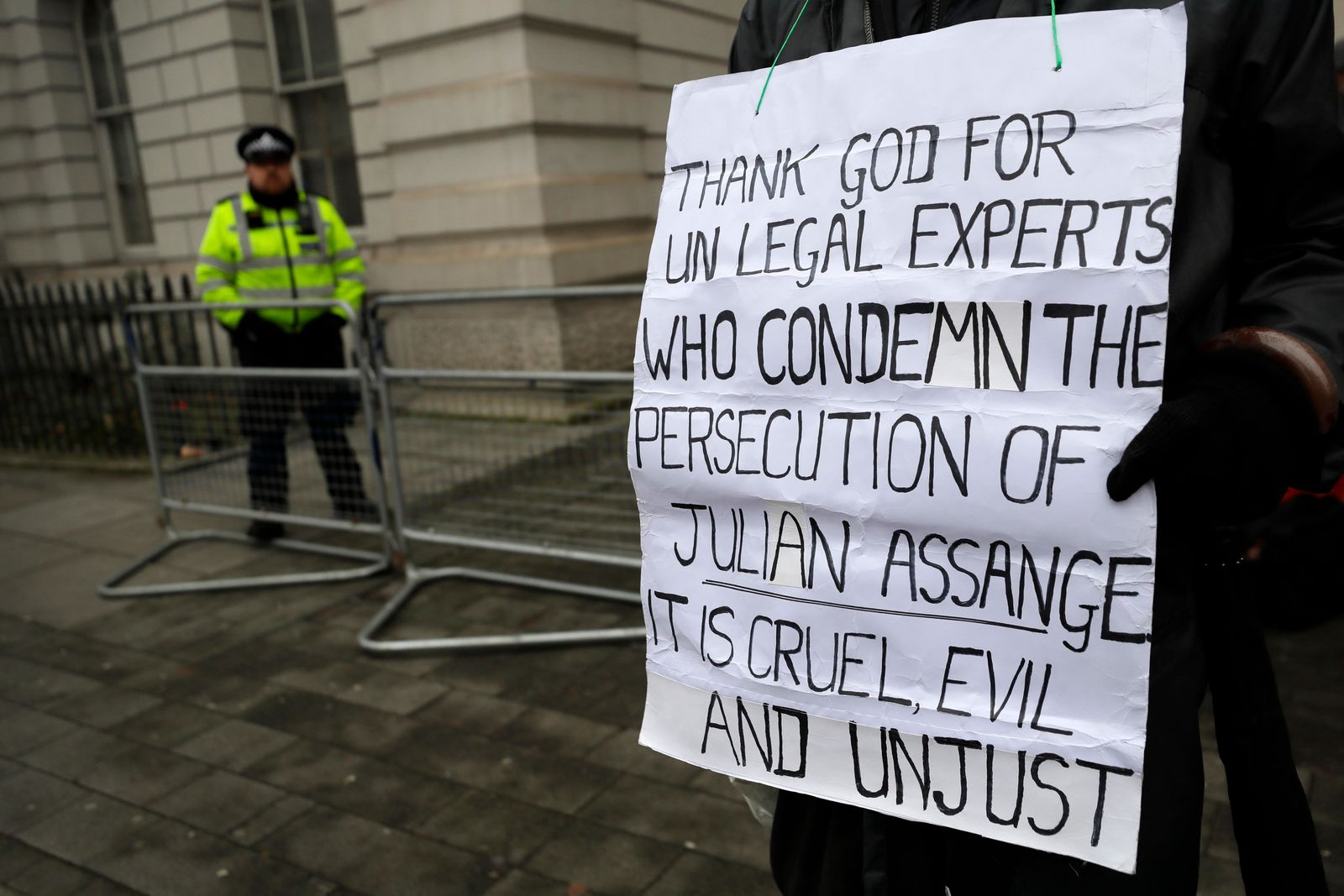 A demonstrator supporting Julian Assange holds a banner outside Westminster Magistrates Court in London, Thursday, Jan. 23, 2020.{ } (AP Photo/Kirsty Wigglesworth)